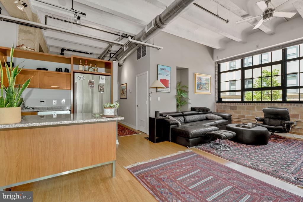 Quintessential industrial loft in the heart of Logan Circle. This two-bedroom, two full bathroom unit has the perfect mix of location and industrial character. The massive triple hung industrial windows allow for light to cascade into the open floor plan showcasing the beautiful hardwood floors that run throughout the over 1,000 square foot unit. Complete with exposed brick, exposed airducts, concrete columns and 12-foot ceilings this unit will have you in awe over its charm and size.  A large and open kitchen offers a granite countertop island with bar seating and plenty of space for cooking prep. The appliances are all stainless steel and include a four-burner gas stove, built in microwave, Bosch dishwasher and refrigerator. The kitchen is open to the living space which is large enough to fit an oversized couch and an entertainment center. Perfect for entertaining a large group of friends or gathering before heading out to enjoy the 14th street nightlife.   The primary bedroom is spacious enough to accommodate a king size bed, nightstands and a dresser. A wall of industrial windows allows for light to pour in on a sunny day but also offers custom Hunter Douglas window treatments for maximum privacy. The primary bedroom is complete with an ensuite bathroom with steam shower and an ensuite walk in closet with custom C shelving. The loft can function as the perfect guest room with full ensuite bathroom or as a home office perfect for zoom calls or even a social distanced in person meeting.    This unit comes with one assigned parking space large enough for a full SUV to park with plenty of room on either side. Conveniently located in the heart of logan circle you are within walking distance to Whole Foods, shops, bars and some of the city's most highly acclaimed restaurants.