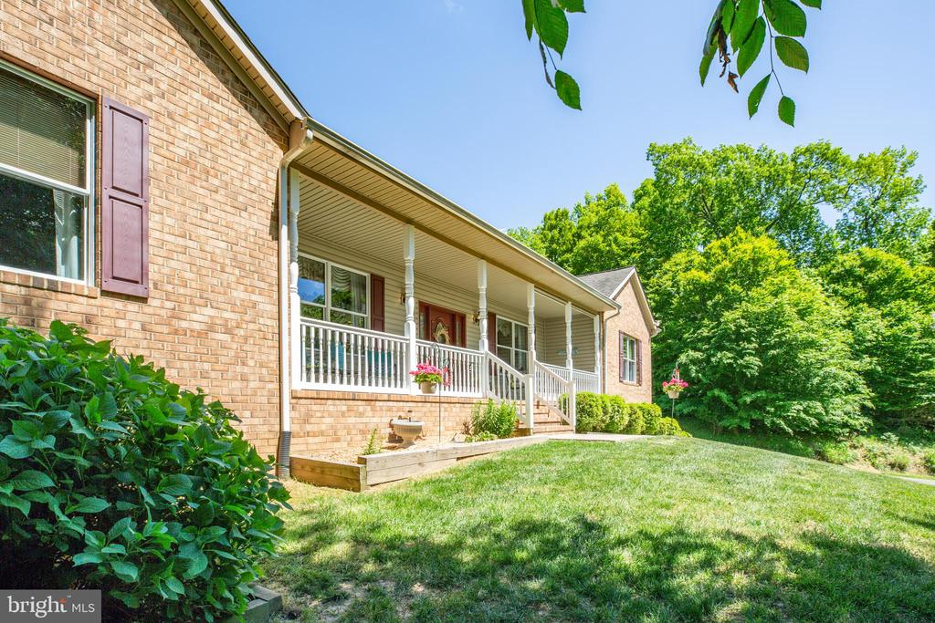 Beautifully well-maintained custom-built rambler that sits on a  private 10-acre wooded lot that is listed under appraised value!!!  A short golf cart drives away from Fairview Beach(Potomac River access).  Large deck and patio with an eight-person hot tub perfect for entertaining friends and family. Over-sized side loading garage with a four-sided concrete storage area under the front porch.  Walk into a spacious dining room to your right and a sitting room to your left.  Spacious primary bedroom with a large, jacuzzi heated tub and his/her closets.  Spacious floor plan with 9-foot ceilings, beautiful hardwood, and carpet flooring throughout.  Eat-in kitchen with a center kitchen island. Gas cooktop and double oven with a large pantry.  Wet bar off the living room with a wine fridge.  Spacious bedrooms with large closets. The basement has additional family room/rec room space.  Walkout basement to back yard. Boat ramp access and a pier for fishing.  This home is situated in a quiet, and relaxing area.
