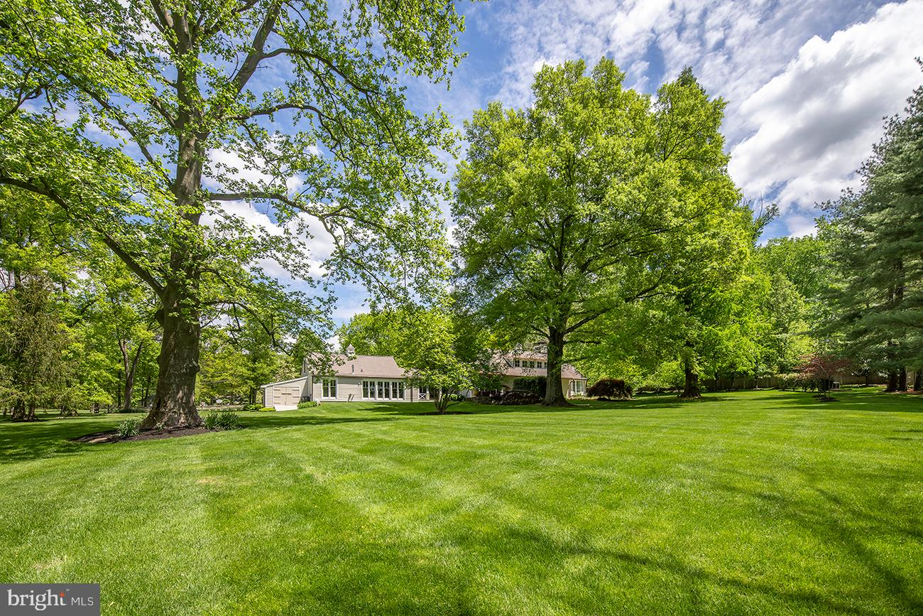 Exquisitely-remodeled modern farmhouse on a gracious 1.77-acre lot in the most desirable street in Radnor Township! Lushly landscaped and light-filled, this 5 bedroom, 3.1 bath stunner is truly timeless, featuring a herringbone oak floor entry, wood-paneled accent walls, soaring ceilings, and richly-appointed spaces built to entertain. Best of all are the scenic views of gorgeous greenery surrounding you that include a lovely stream. At the heart is a show-stopping, custom crafted kitchen by Smallbone of London – a world-renowned master craftsman and bespoke design firm. Fit for a chef, it's styled with top-of-the-line appliances including a Wolf range, Sub-Zero refrigerators & Miele dishwashers, plus ample custom cabinetry, 2 quartz waterfall islands, and easy access to a generous outdoor patio through floor-to-ceiling glass double doors. An abundance of natural light bathes the interiors, and exclusive designer touches throughout really take this house to the next level. Create memories in the elegant formal dining room with wood paneled and glass walls, anchored by a vaulted and beamed ceiling and chandelier illuminating a soft glow. Host a crowd with ease in the den with built-ins and French doors, or retreat to the great room with a stately wood-burning fireplace, custom millwork, and 3 sets of French doors bringing the outside in. Not a single detail is left unturned! Start and end your days in the warm and inviting main-floor primary suite. Your retreat affords picturesque vistas, a charming bay window, fireplace, French door private patio, herringbone floors, and luxurious spa bath outfitted with European fixtures, double sinks, freestanding tub, plus oversized glass shower. Guest rooms are equally comfortable and spacious, residing on both the east and west wings for privacy, boasting character-filled elements from chic wall coverings to designer tiled baths.  Additional highlights include a unique loft bedroom with flex space for a reading nook or art stud