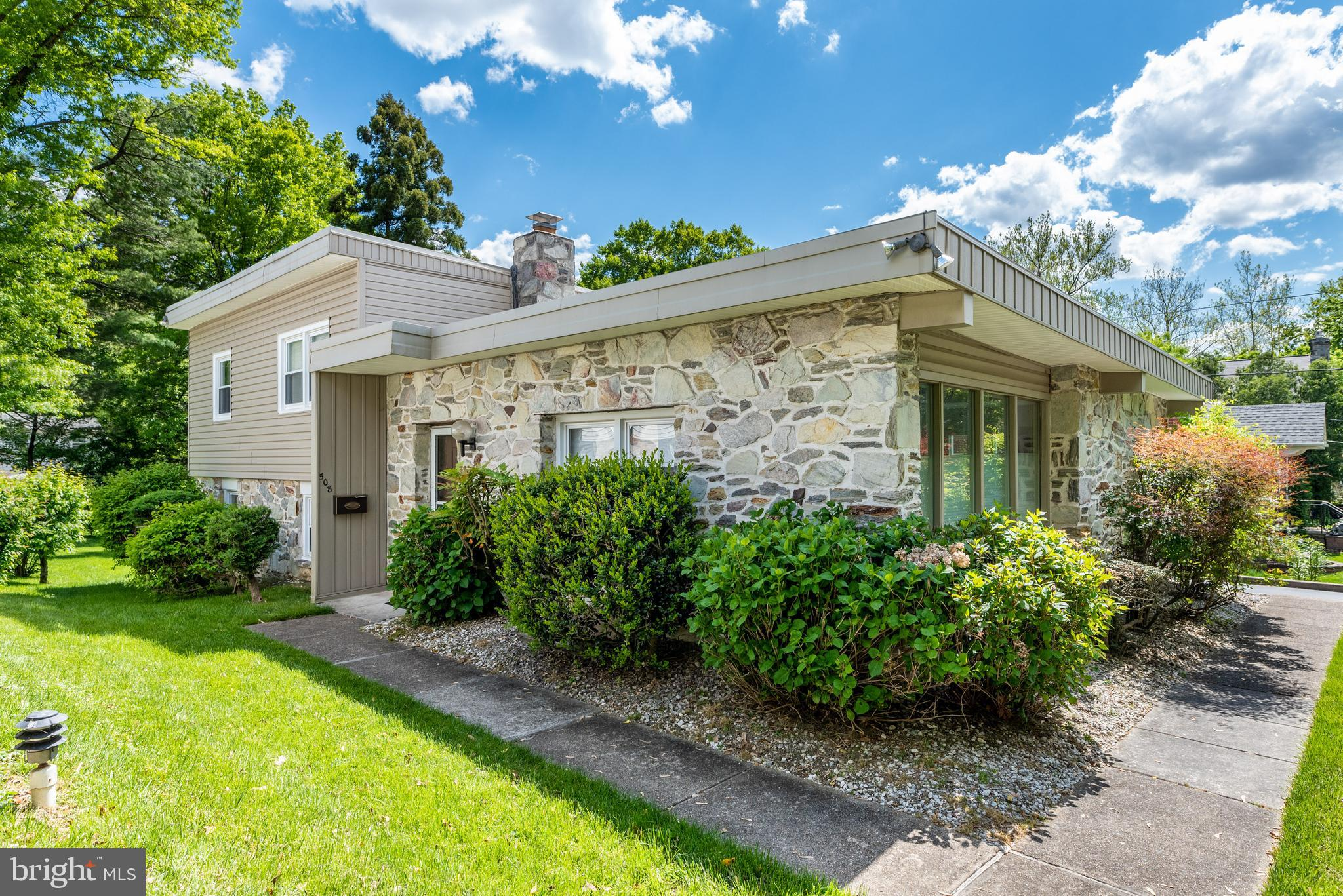 This modern and stylish split-level home in Narberth is just minutes from Montgomery Avenue and all that it offers, and a short stroll to the boroughs unique charms, including its playground and library, as well as unique boutiques along Haverford Avenue. An arresting circular driveway with plentiful parking and pretty front lawn lead to this home, which is set back from the street. Once inside, the open living room and dining room, showcased with walls of windows, beckon. Glowing hardwood floors and recessed lighting make both of these rooms so attractive and inviting, with plenty of natural light streaming in. In the kitchen, which flows well from the dining room, the warm, welcoming vibe continues. Creamy cabinets with pretty hardware, along with a unique backsplash, complement the stainless steel appliances and tiled floor. Step down to a comfortable, carpeted family room, with recessed lighting and a ceiling fan. Sliders lead outside to the pretty patio overlooking the lovely backyard and storage shed. Steps lead to the second level, with its main suite, two additional bedrooms, and hall bath. The main bedroom, with hardwood floors and ceiling fan, is spacious and comfortable, while the en-suite bath is sumptuous. Remarkable tiles flank the glass-doored, step-in shower, and the vanity has a pretty granite countertop. The two additional bedrooms are comfortable, each with windows and closets. The hall bathroom has a tub/shower combination, as well as a vanity sink with attractive countertop and plenty of cabinets. The large, finished level steps below the family room is a fun recreation space, with a built-in toy chest. It also houses mechanicals, as well as the laundry area. There is a pretty powder room on this level, with a deep vanity sink. Outside, the nice patio overlooks the expansive, green and level yard and handy storage shed, and the driveway and one-car attached garage provide plenty of parking opportunities.   The borough of Narberth has numerous at