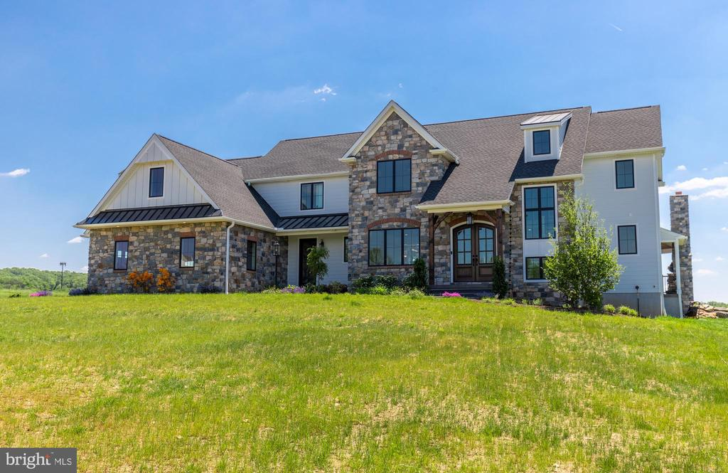 Welcome to 2140 Seven Oaks Road! Nestled on 5.71 secluded acres in Charlestown Township and Great Valley School District, this like-new luxury home offers amazing customizations at every turn. Step into the grand, 2-story foyer boasting beautiful hardwood flooring that spreads throughout the main floor. Off the entry is the formal dining room with wainscoting and crown molding, perfect for hosting large or small meals. The open floor plan of the kitchen and family room make this home an entertainer's dream. The gourmet kitchen features an abundance of custom London Grove cabinets, quartz countertops, upgraded stainless steel appliances, an expansive island with breakfast bar and storage, double oven, recessed lighting and a large butler's pantry with beverage fridge, ice machine and tons of storage space! The sunny breakfast area offers access to the rear patio and opens to the grand family room with custom wood beams, gas fireplace with stone mantel and a wall of sliders to create an indoor/outdoor oasis! Take advantage of the main floor study offering french doors and tons of built-in storage cabinets and shelving. A convenient mud room and two powder rooms round off the main floor. Ascend to the second story and find the grand master retreat featuring a vaulted ceiling, tons of light pouring in from the large sliders that lead out to the Juliet balcony, double walk-in closets, and an impressive master bath with dual vanity, soaking tub and a custom tile shower with dual rain showerheads. There are 4 additional, generously sized bedrooms, with two offering their own baths, and two bedrooms sharing a Jack and Jill bath. All of the bedrooms feature a walk-in closet! The second floor is completed by the laundry room for your convenience. The huge walkout basement offers tons of additional storage space and potential for additional living space with a finished bathroom and gym area! The amazing features of this property do not end inside! Entertain your guests on the 