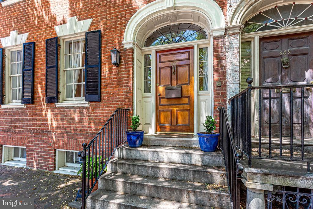 """Built in 1780 this home offers a true piece of history!  Gorgeous and restored with over 230K worth of improvements, this end unit/semi-detached Federal Brick row home was once home to Robert E Lee's father General """"Light Horse Harry"""" during the early 1800's.  The home offers original features in addition to a 1912 remodel with details that have been meticulously preserved and treasured!  Hardwood floors, crown molding, base moldings and stunning architecture.    Centrally located in the Heart of Old Town Alexandria's Historic District, this one of a kind home offers 4 private parking spaces, a beautiful fenced outdoor garden and patio lined with fruit trees.  The home offers front, rear and garden entrances,  The front and rear of the home are joined by a center vestibule as well as the lower level basement suite can be accessed from the center vestibule or privately from the outside garden entrance.   Renovations include NEW wood roof and copper gutters and downspouts, HVAC, Lower level and garret levels fully remodeled,  as well as historically restored glass windows, 7 re-lined chimneys, preserved and painted moldings and completely renovated bathrooms and updated kitchens!  This unique home offers almost 4200 sq ft of living space and has the opportunity for multi generational living  and great work from home space!  The front of the home offers a Living room and kitchen, Primary suite with fireplace and attached den, 2 guest bedrooms and 2 1/2 baths.    The rear of the home offers the perfect setting for a formal dining room with restored fireplace another private kitchen, private laundry, as well as a full dining room, living room and 2 bedrooms with renovated bath.  This beautiful historic home offers a one of a kind living experience with ample entertaining space that your guests will fall in love with."""