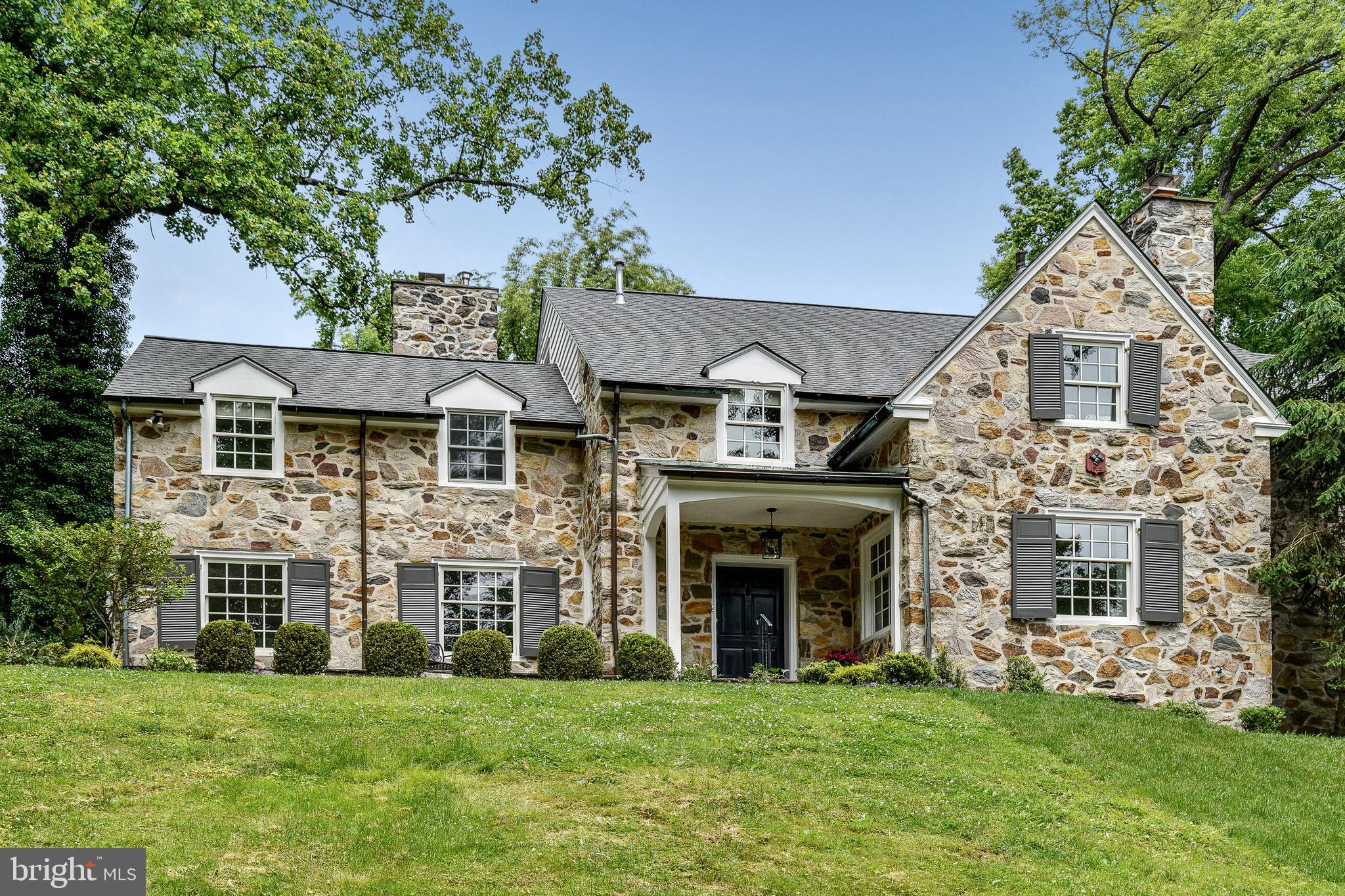"""This is a modernized 1-acre stone home that pays respectful homage to its original 1940 classic Main Line roots. Enter up to the home from the long private driveway through the original stone pillars etched with """"Indian Hill"""" as the home was nicknamed by its original owners' son who used to find stone arrowheads all over the property as a boy. This five bedroom, three full/two half bath home has space for everyone and more. The first floor has large sunny rooms and a redesigned floor plan with amazing flow. The living room offers deep-sill windows, fireplace with classic mantel and marble surround plus a large sunny bay window. The private library / home office is full of windows and a second fireplace. The spacious formal dining room too has a bay window and it transitions to the fully fitted butler's pantry complete with Fisher Paykel dishwasher, bar sink, bev/wine refrigerator, and ice cube maker along with tons of cabinetry. Continue to the beautiful open-concept kitchen, planned so that it is efficient for the cook. The kitchen includes professional Viking stove, newer dishwasher, new 42"""" refrigerator, microwave drawer, warming drawer, classic white cabinetry, stone backsplash, stainless farm sink and soapstone Silestone counters. The Carrera island has its own filtered water. The accompanying family room is lined with windows, built in surround sound and a desk area that leads to mud room. A back stairway leads up to the second and third levels. Upstairs the master suite is bright, sunny and boasts a bay window overlooking the gardens, plus it's own private deck, and a dressing area with a custom-fitted walk-in closet. The massive seamless glass master bath shower is state-of-the-art, with two walls full of nozzles, showerheads and two vanities. A second large master with en-suite bath also has access to the second-floor deck.  Completing the second floor are two other large sunlit bedrooms with generous closet space and jack and jill bath. On the top floor, a"""