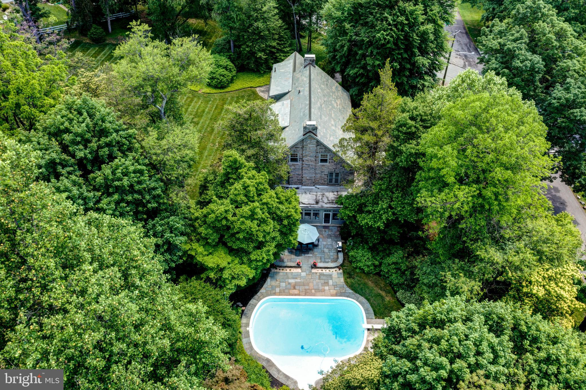 Perched above a quiet canopied corner, just steps from the foot trails of Carpenter's Woods, you will find the quintessential Wissahickon schist center-hall Colonial. Sitting on almost an acre and a half the 8,000 square foot home seamlessly integrates the old and new in creative ways that are both modern and timeless. Upon entering the home, you will be greeted by a gracious hall featuring gorgeous restored hardwood floors, soaring ceilings and a statement grand staircase. To the right of the foyer is the formal dining room with a feature fireplace and wall length window seat. A set of french doors lead to the sunken sunroom soaked in light which is the perfect retreat for a quiet morning coffee or a good book. The chef's kitchen features a paneled refrigerator, double wall ovens, and a long center island with room for seating. A breakfast nook and a wall of built-in cabinetry complete the kitchen. On the opposite side of the entry is the spacious living room, which includes classic millwork, twin arched openings with pocket shelves and a double sided fireplace bookended by two sets of french doors. The double doors lead to a bright and cozy family room with a beautiful stone wall that reminds of Valley Green. The comforting space offers direct access to the newly laid bluestone patio which opens to the enchanting salt water swimming pool and lush garden with wrought iron surround.   The second level includes a stunning main suite. The primary suite features a wall of built-in closets, custom dressing room with an abundance of detailed storage, a small center island and recessed lighting. The ensuite bathroom rounds out the space, with marble throughout, dual sinks, a soaking tub and glass enclosed rain shower. The convenient home office and matching set of Jack and Jill suites balances the second level. The third floor hosts a large completely renovated great room with a wet bar, half bath and plenty of space for entertaining and gaming. Additional flex space incl