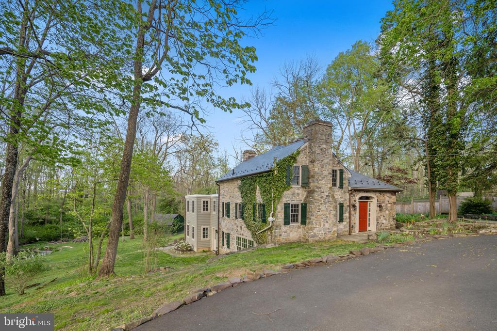 """Tucked into Solebury's prime Aquetong Valley within eyeshot of a stunning stone-arched bridge, this three-level, English-style 1650 stone cottage  has had some major updates: NEW slate composite roof with copper gutters and copper snow guards; ALL BRAND NEW windows (even the """"newer"""" ones were replaced), brand new refrigerator, BRAND NEW sumptuous Main Bath AND SO MUCH MORE!!! Deep windowsills, exposed-beam ceilings, 3 beautiful fireplaces  and exposed stone walls add visual interest and texture inside. Outside, extensive tiered, natural-stone patios and a party-sized deck overlooking the rear yard provide plenty of outdoor space for warm-weather enjoyment. The main kitchen/dining area is open with high ceilings, substantial crown molding, recessed lights and French doors opening to a patio and the deck, very convenient to the kitchen for those who enjoy grilling. The kitchen's newer cabinetry, Wolf professional-grade 6 burner range with stainless exhaust hood, built-in Sharp microwave, Bosch dishwasher with cabinet panel, and brand new stainless armoire-style refrigerator/freezer and Quartz countertops complement the character of the house. A handsome porcelain farmhouse sink, breakfast bar and pantry complete the kitchen area. The dining area with fireplace is expansive, able to accommodate plenty of friends and family. The living room with fireplace is divided by the stairwell, a convenient arrangement if someone wishes to watch TV in one area and have a quiet space in the other. Upstairs are two bedrooms that share a Jack & Jill bath with custom shower finished in slate tile with rainfall showerhead and handheld, and vanity with undermount sink. The daylight walkout lower level presents flexible space finished with a bluestone floor. The sizeable main room has a large fireplace and big bay window. A beautiful full bath with tub/shower is nearby as are two additional rooms (fourth bedroom and office or workout space) and a laundry room. A French door opens to a lo"""