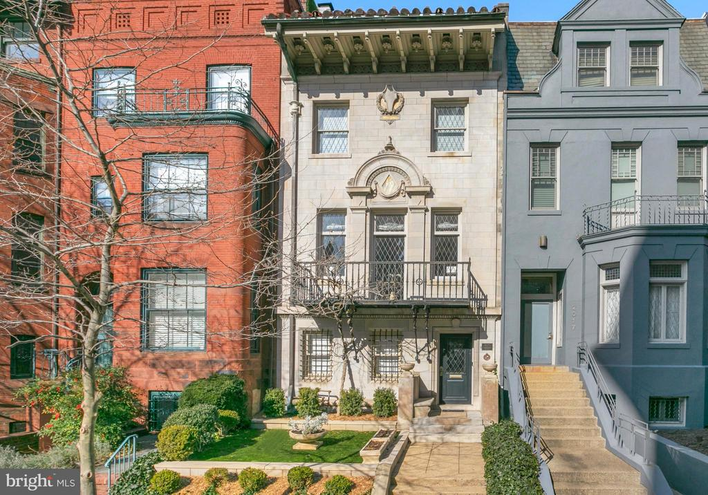 This historically significant circa 1910 Italian Renaissance Revival townhouse is located in the heart of the Dupont neighborhood. Originally built by prominent American architect Waddy Wood as his personal residence, the house offers dramatic and impressive architectural elements. Wood is most famous for his works including the Woodrow Wilson House and the Main Interior Building, formally known as the Steward Lee Udall Department of the Interior Building in Washington, DC. The house has been superbly renovated and offers a flawless blend of original architectural details fused with modern-day conveniences and design. It features an abundance of natural light from large windows, which is magnified by the high ceilings throughout. There are grand-scale entertaining spaces, three of which have lovely marble fireplaces. There is also a newly installed elevator, which services all four interior floors. The entry is graced with a newly renovated front vestibule with beautiful marble floors and a glass paneled door to the lovely foyer and entry hall, which is ornamented with stunning new chandeliers. The front parlor with fireplace is perfect for entertaining, enhanced with an abundance of southern sunlight and providing a convenient powder room for guests. Towards the back of the residence is a large family room with a gas fireplace and a private bedroom with an en-suite bathroom. There is also a newly expanded storage closet on this level. The grand central stairway to the second level provides a dramatic admittance to the floor above. The second level has nearly 11-foot ceilings and offers a stunning living room with a front balcony overlooking the splendid architecture of the historic street below. There is an additional powder room on this level and a transitional hallway to the formal dining room. The dining room features a double arch wrought-iron door and leads directly to the fully renovated gourmet kitchen. The kitchen offers a large center island, high-end appl