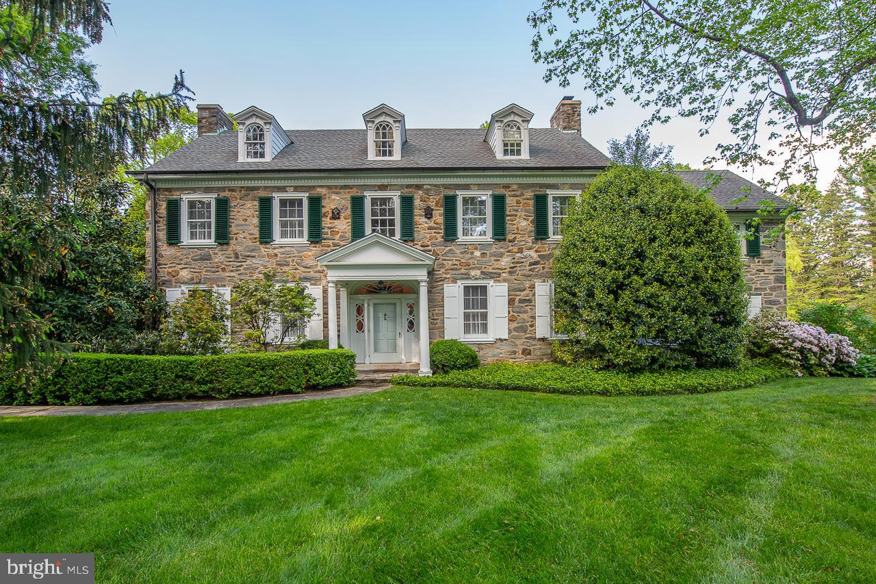 This Impressive Stone Colonial Manor Home is an Architectural Masterpiece and Horticultural Dream. This home sits prominently on an exceptional 2.26 acre lot in the heart of the prestigious North Rose Lane neighborhood in the community of Northside Haverford.  Dating back to 1935 this exquisite home features old world charm, unparalleled craftsmanship, beautiful woodworking and many updates thruout.  Interior features include an impressive Thru Center Hall with stunning staircase and winding balcony flanking the entrance to the Formal Living  Room with Fireplace and the large elegant Dining Room also with Fireplace. The Living Room leads to a stately mahogany study/ den with beautiful fireplace with stone surround, and built ins and French door to lovely brick patio with stone walls overlooking magnificent grounds. The Dining Room leads to large Butlers Pantry with an abundance of white display cabinetry and stunning brass bar sink adjoining an expanded white kitchen with large granite island and ample white cabinetry and breakfast and desk area with large sliding glass door overlooking magnificent courtyard and grounds and access to three car garage. Second Floor features a large master suite with wood burning fireplace and adjoins sitting/ dressing room/ office. Multiple Bedrooms and adjoining baths are on the second level. Third floor offers 2 more bedrooms and 2 baths or large upstairs family area. The exterior of this wonderful home offers total privacy and magnificent mature landscaping , impressive gardens blooming at all different times, plenty of room for a pool and/ or court, a charming front portico entrance, an expansive rear brick patio with stone walls overlooking courtyard gardens and exceptional grounds. The versatile floor plan and wonderful flow make this home perfect for both active family living as well as elegant entertaining.  Offering many new amenities combined with the charm and elegance found only in an older home, this exceptional home is 