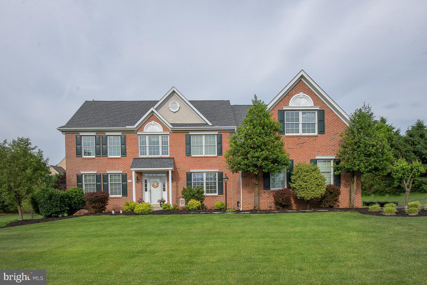 """Welcome to 716 Yarmouth Drive, a gorgeous brick front Jamestown model in the sought after community of """"Clocktower Woods"""" in East Goshen. Situated on a private level lot, this neutrally decorated & beautifully appointed home offers over 5,000 square feet of living space on 3 levels featuring 5 Bedrooms, 4 full Baths and 1 half Bath including a professionally finished Lower Level w/Game Room, Media Room, Exercise Room, large custom Bar area w/wet bar sink, 2nd Home Office & full Bath. Recent 2021 updates include freshly painted interior & exterior, refinished hardwood floors, new Recessed Lighting, new Side Porch, new landscaping and an updated, refinished deck. Extensive custom millwork throughout 1st & 2nd floors includes crown molding, chair rail, dentil moldings and wainscoting plus custom blinds throughout. 1st Floor features stunning 2-story Foyer w/hardwood and turned staircase; Dining Room w/hardwood, Living Room w/hardwood, private Study w/hardwood; magnificent 2-story Family Room w/feature windows, slate surround gas Fireplace & family back staircase; renovated Gourmet Kitchen/Breakfast Room features additional custom cabinetry including new glass cabinets, hardwood, granite countertops, stainless appliances including 5-burner cooktop, built-in microwave & double wall oven plus oversized custom Island; Powder Room, Laundry/Mudroom w/sink & cabinetry complete main level. 2nd floor offers large luxury Master Suite w/walk-in closets, Master Bath featuring deep soaking tub, oversized tile stall shower & separate vanity sinks; 4 additional family Bedrooms including large Princess Suite w/en-suite bath also accessible to the hallway and Jack 'n Jill Bath for Bedroom 4 and 5. Additional amenities include 3-car garage & large rear deck. Don't miss this fabulous home in the award-winning West Chester School District and close to the area's finest private schools. Convenient to Malvern & Paoli train stations, the shops and restaurants of downtown Malvern, West Cheste"""