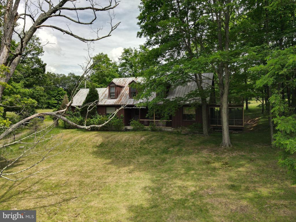 Need a Get-A-Way or Farm?    This 34.19 acres (4 lots) has privacy, mountain view and even your own private air strip (Buzzards Gap Ultralight Flight Park).   Home features 2500 square feet of living space.  4 bedrooms, 2 baths, kitchen, dining room, living room, great room with fireplace with woodstove insert, and family room.   Bring all  your friends and family to enjoy the country life.   Situated off a state maintained road for easy access.   Close to Cacapon State Park where you can play golf, swim & fish in the lake, go horseback riding, etc.    Drive to  downtown Berkeley Springs where you can enjoy dining, spas, shops, antique shopping and so much more.