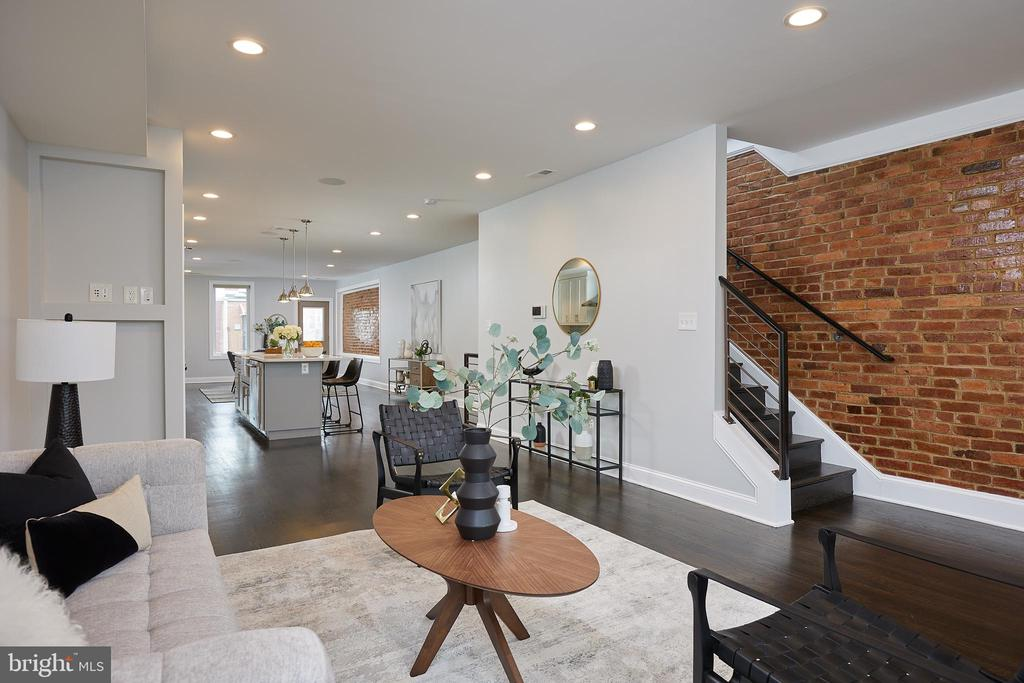 This is the ONE you've been waiting for! Truly exceptional in every way, this 1900+ sq ft 3br, 2.5 baths exceeds expectations. Boasting an excellent floor plan, this voluminous open space is flooded with light from its southern exposure. Gleaming wood floors, walls of exposed brick, a gorgeous central kitchen with terrific cabinet and counter space, and an incredibly functional center island.  Beautifully balanced, the living room and dining room are perfectly perched on each side of the kitchen, as is the all important main floor powder room. A much sought after home office area sits adjacent to the dining room and is a great spot to work from home. Access to the rear of the property is directly off of this area and leads to the highly prized secure parking space.   An expansive primary bedroom suite is sure to impress with its oversized bath and excellent closets. The second super large bedroom is styled with a dramatic turret and more desirable closet space. A flexible 3rd BR/den/office sits right at the second floor landing, as does the stylish second full bathroom. Easy stairs lead to a STELLAR PRIVATE ROOFDECK with sweeping 360 degree city views. It's truly fantastic!  This well manicured boutique building is pet friendly and has an attractively low condo fee. Super close to the METRO & all that Eckington and Bloomingdale area has to offer including but certainly not limited to Red Hen, Boundary stone, Big Bear Cafe, Sylvan Cafe, Yoga District, Harry Thomas Community Center/pool.