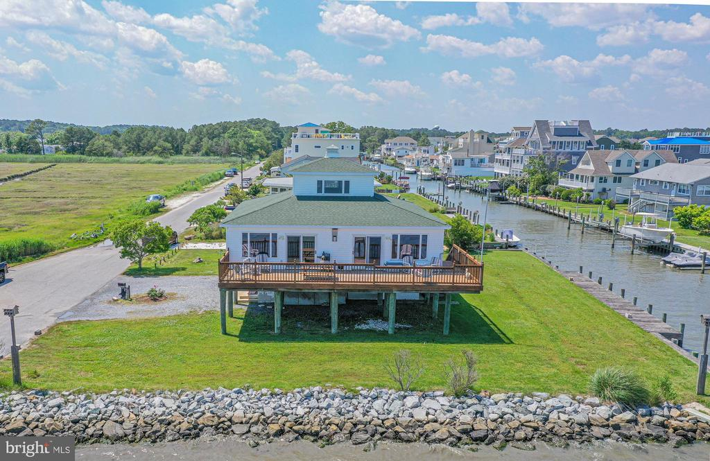 WOW! Rare Find-Custom built direct bayfront home overlooking the Sinepuxent Bay, Assateague Island, and the Atlantic Ocean!! This unique home designed to resemble the Chesapeake Bay lighthouse features a large bayfront deck, boat dock, boat ramp and extra large lot!! Interior features include, water views from every window, spacious open floor plan, 2 large bedrooms on the main floor and a loft with spectacular 360 degree panoramic views could be used as a 3rd Bedroom. HVAC and roof have recently been replaced. (( Sewer fee $328 per Quater )  Located in the picturesque, tranquil, neighborhood of Snug Harbor within 5 miles of Assateague and just 3.1 miles from the OC inlet with no bridges- You'll enjoy majestic moonrises, sunrises, rainbows, nature views, boating, fishing, water sports and all of the nearby amenities of Assateague State & National parks (home of the wild ponies), Ocean City beaches and boardwalk, world-class golf courses, family and fine dining, amusement parks and main street Berlin, (voted Coolest Small Town in America)! No City Taxes and HOA is voluntary for just $40 annually!