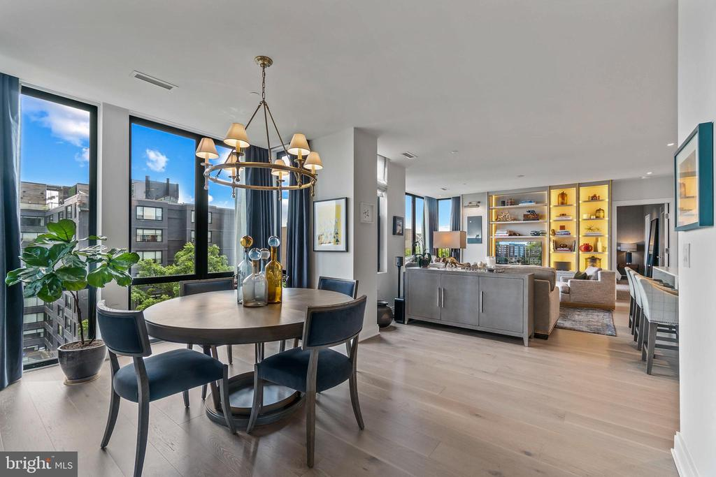 Picture-perfect residence with custom finishes galore at The Elysium in vibrant Logan Circle. With a near perfect WalkScore, a car is not needed but this unit comes with one of only five coveted garage spots in the building. Ascend up the private elevator which opens directly into unit 701. The home's front-facing location and massive floor-to-ceiling windows create a backdrop of full southern exposures and great city views throughout the quiet home. Luxe finishes surround you in the massive open layout where every gorgeous detail was professionally designed by J.D. Ireland and has been meticulously maintained by the original owner. Nine foot ceilings, Kahrs hardwood flooring, and stunning built ins frame the grand 1800 square foot layout with a den, amazing storage, and a rare full laundry room. The sleek open-concept kitchen is a home chef's dream with Thermador and Bosch stainless steel appliances, Poggenpohl cabinetry, Calcatta vintage quartz waterfall countertops, a full-sized wine refrigerator, and an oversized island with seating. The exquisite bedrooms are bright and spacious with a custom Stark rug and designer Philip Jeffries wallpaper in the primary. Opulent bathrooms with Porcelanosa tile, soaking tubs, and custom vanities provide a spa-like experience at home. Owners at The Elysium Logan enjoy the best in boutique living with only 32 units and luxurious common areas. The modern lobby with a private concierge is perfect for assistance and securely receiving deliveries. The quiet residential street is adjacent to all the excitement that 14th Street has to offer with a dining, shopping, and nightlife mecca at your doorstep. Quickly check off your errands at Whole Foods on the next block and spend the weekend wandering with a never-ending list of things to see and do. Dupont Circle and U Street Metros are nearby for easy commutes around town.
