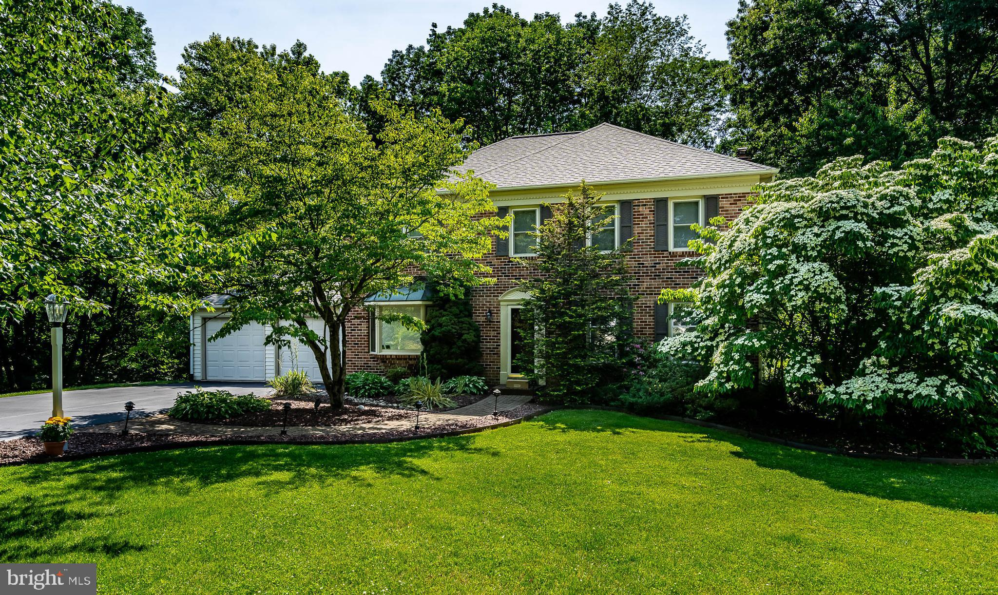 In a park-like setting, on a quiet cul-de-sac, this brick front Colonial's exquisite curb appeal is just the beginning.  Enveloped by lush flowering greenery, its 3/4 acre lot affords privacy and plentiful area to play, entertain, or simply sit back and enjoy the surrounding natural beauty.  Just off the hardwood entry is a large living room that can handily double as a playroom for families needing less formal and more casual living space.  The formal dining room features hardwood flooring and a lovely bay window. The eat-in kitchen shines top to bottom, with abundant recessed lighting and gleaming hardwoods.  A center island offers additional workspace as well as barstool seating for two.  A double sink, tile backsplash, smooth cooktop range, dishwasher, custom built-in refrigerator, generous white cabinetry, built-in desk/nook, and large pantry all combine to provide for easy meal prep in a fresh-as-spring-like atmosphere.  Immediately adjacent to the casual dining area, the family room keeps the light, bright vibe going with an all-white gas log fireplace brick surround and natural light flowing in from the French doors that connect to the spectacular outdoor living spaces.  The opposite side of the kitchen conveniently provides a combination mudroom/laundry room with garage access and an adjoining powder room.  The washer and dryer convey with the home.  Upstairs, enjoy restful nights and refreshing mornings thanks to four generously sized bedrooms and two full baths.  The primary bedroom with ceiling fan, new skylight, oversized window with nature view, has a private bath with dual vanity and large step-in shower.  Three additional bedrooms also feature ceiling fans and share a full bath with double sinks and tub/shower combination.  The daylight basement, with sliders to the back yard, has been finished to provide welcome extra space for a recreation or media room, a place to set up a personal gym, and plenty of storage space.  Outdoors, family and friends ar