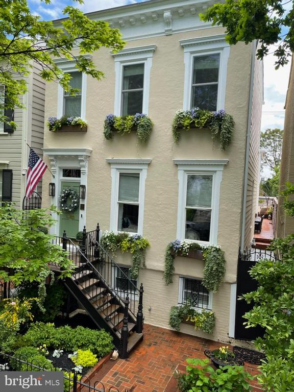 Lovely tree-lined neighborhood block in center of West Village near shopping and best restaurants. House is a partially detached Federal style home originally built in 1850 with 4 BR's and 4 1/2 bathrooms; all bedrooms ensuite with walk-in closets and hardwood floors throughout. Renovated in 2019-2020, there have been no finishes or amenities overlooked; this house is perfect for a couple who loves entertaining or a larger family.   The top floor features an optional private suite with large walk-in closet which has a built-in desk/vanity and stacked washer/dryer for owners' convenience. Primary bedroom also includes access via bathroom to tons of storage space in partially finished attic. The second staircase in the rear of the house gives direct access to two additional bedrooms from family room. Additionally, there is a windowed basement bedroom with private front entrance that could easily convert to a fantastic au pair suite with the basement's full sized laundry room that is alternately plumbed for a kitchenette. The bright eat-in kitchen on the main floor provides tons of natural sunlight and includes a Wolf range, additional in-wall oven, wine fridge, and wet bar second sink.   The house has been upgraded throughout with interior and exterior wiring for Sonos Sound System with ceiling speakers throughout first floor and primary bedroom/bath. The house also has been updated with Lutron lighting system, a front-yard sprinkler system, on-demand hot water heater, radiant flooring in primary bedroom and kitchen, and decorator designed window treatments and plantation shutters. The house has a private, fenced front yard featuring custom copper window boxes and bricked rear/side patios, with access to the private one-car garage, which have been meticulously landscaped for outdoor entertaining. An optional 2nd parking spot in the rear alley is available via rental from a neighbor.