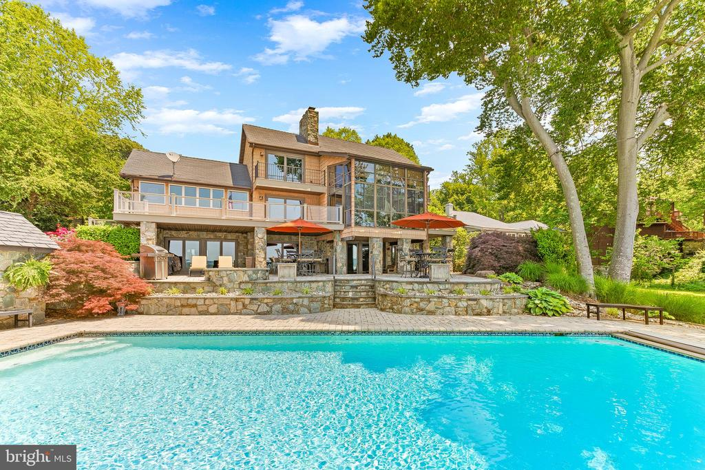 """Once in a lifetime waterfront opportunity in Huntingtown on the Patuxent River! This one-of-a-kind waterfront property has been family owned for 30 years. Every single room in the main house has unobstructed water views with surreal sunsets. The back patio will treat owners and guests to a truly special resort-like experience, with one of the best pool locations on the river and 180 degree views of the water.    There are a total of 7 bedrooms, 5 full baths & 2 half baths on the main property parcel, which is approximately 1.6 acres. 4/5 bedrooms in the main house, 3/4 bedrooms in the detached garage apartment. Additionally, there's a detached custom stone garage, which can shelter 12-14 cars without lifts. This property could not be recreated at the list price. There is also an opportunity to purchase the neighboring property (not included in list price), which would complete a truly unique waterfront family compound on approximately 3.5 acres. Both properties are completely fenced by a ten foot privacy fence, complete with individual gates to access both properties separately.   Main Features:  1) Custom Stone Main House - Approximately 6,000 sq ft of living space w/ fully finished walk out basement. 4/5  bed, 3 full bath, 2 half baths. 2 car oversized attached garage. Water views from every room (including basement). Updated bathrooms (full steam shower in basement) and updated kitchen. Gym (which could be a pool house bar w/ full bath). Massive stone fireplace with a fireplace on each level for a total of three. The backyard features resort-like stone and paver hardscaping with pool, stone pool pump shed, custom hot tub patio, and fire pit. One of a kind waterfront gazebo. Maintenance free exterior 7"""" split cedar shake look (vinyl). All doors & windows facing West have been replaced with sunshade heat protection shield. Utilities feature a closed loop geothermal system. 45 KW Generator powers every building and utility during an outage.  2) Two Level Detached ga"""