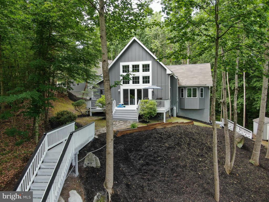 Tranquility at its best!  Perfect lake house and private getaway with 3 large Master Bedrooms and Baths, screened porch, new addition and a one-bedroom apartment above oversized 2-car garage.  Plenty of room for extra guests!  Kitchen features new quartz counter top, breakfast bar and seating, open  floor plan to dining, living area w/gas fireplace, and new addition family room or Bedroom with bump out and sliding barn door.  Waterfront features a new covered dock w/storage with electric lift, and 2 floating jet ski platforms.   Deep water for high-end Sport Boat!  The exterior of the home  has beautiful Board and Batten Siding, detached oversized garage w/Apartment above, matching shed and a nice staircase to waterfront!  Two fire pits, play ground area with a climbing hill and blocks.   Plenty of fun awaits you and your family!   Owner has added many upgrades to the home inside and out such as a newly Paved-lighted driveway and parking area, a nice Golf Cart path to the lake, and landscaping.  Seller will offer Purchaser first right to purchase boat and jet skis.
