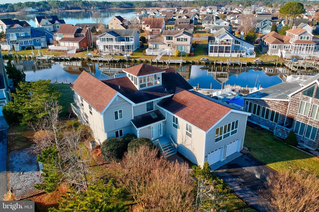 Almost 3000 square feet and situated on a beautiful .40 acre waterfront lot in Wood Duck Isle II in Ocean Pines. The home offers a large waterfront backyard and deck and lots of windows to enjoy the water view. Downstairs you'll find hardwood flooring in the living room and sunroom. A wood burning brick fireplace. An eat-in kitchen with water views, island in the kitchen and large laundry room/mudroom leading to the attached two-car garage. Also downstairs are 2 bedrooms, 1 full bath and one 1/2 bath. On the second floor you'll find the master bedroom and large master bath, a loft overlooking downstairs that's perfect for home office space, as well as a massive bonus room filled with natural light over the garage (used as an art studio). A spiral staircase takes you up to a widows peak/solarium good sized room filled with windows and natural light to capture the water views. A long driveway offers ample parking and leads to the oversized 2 car garage with lots of storage. At the waterfront, there is a long boardwalk and lateral dock with mooring poles and fish cleaning station. The location is a gem and  it's ready for the right buyer to do some updating and make this house their home! Home sold As-Is.