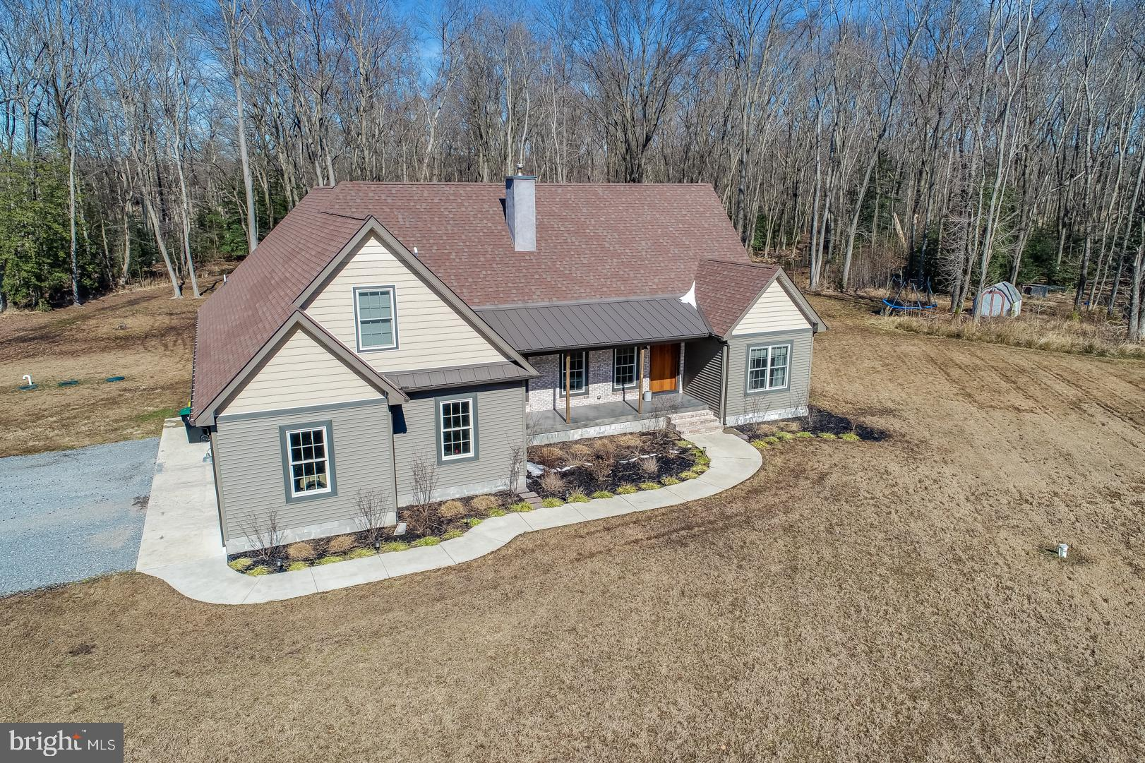 Looking for a little piece of heaven? Well you just found it. This custom built 3883 square foot, 4 bedroom 3 bath home sits in the middle of 10+/- acres of wooded land loaded with everything nature has to offer. The 10 acres includes a 6 acre parcel and a 4 acre parcel (9-00-07200-01-6300-000). There is also a 2 acre parcel that can be purchased separately. It's hard to know where to start. From the time you pull up the driveway you can see all the love and care that's been put into this home. Greet your guest at the  4x8 ft 2 inch  custom Mahogany front door as they wait on the covered 6x28 stained concrete front porch. Walk into the living room of this beautiful open floor plan and enjoy the warmth of the zero clearance wood stove with custom mantle, stained concrete hearth and modern ship lap accent wall. Engineered oak hardwood flooring is throughout the living area of the first floor that leads into the eating area and kitchen. The custom Amish built cabinets have soft close drawers and doors. You'll love the look of the stainless steel farm house sink, stained concrete countertops with tiled backsplash and stainless steel appliances. There is also a hidden 4x13 pantry for additional storage. The kitchen island is fitted with a custom Maple counter top. You can sit at the dinning table and look out your French doors overlooking the covered porch and spacious back yard. There is a first floor master with 9x11 walk in closet with custom closet organizer, a sitting area and full bath with walk in shower,and a soaking tub. Glass door to be installed on Master bath Shower.   Two additional bedrooms, 9x8 laundry room, another room currently being used as an office  are also on the main floor. The extra wide hallway with custom locker area for coats and shoes for each member of the family leads you to  your inside access to the over sized  26x27 garage with custom oversized cypress overhead doors . As you top the stairs to the second floor the first thing you'll notice is the unique Epoxy floor in the 20x30 family room. There is also an 18x30 play room, a 4th bedroom and a full bath. All of the bedroom closets on the main  level have custom organizers and all interior doors are solid core raised panel doors. With dual heat and AC zones you can be comfortable both  downstairs and up. This all sits on top of a conditioned crawl space, Now let's take a journey outdoors to the 40x60 outbuilding that is currently being used as a shop for a home based business. There is also a 26x17 bump out that could be used as a showroom or offices and there is also a 7x14 bump out. The entire building is heated by radiant floor heat generated by an outdoor wood stove. The outside of the outbuilding is tastefully covered with Cypress siding. Custom built, amazing, comfortable and peaceful are just a few of the words you could use to describe this home. Put this one on your list of homes to see today.