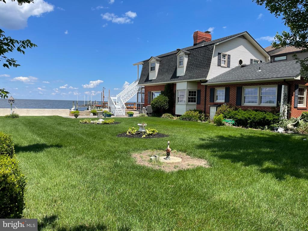 Wow! This waterfront home offers a rare opportunity to fully enjoy The Land of Pleasant Living.  Located on a desirable double lot at the end of Lake Drive, this house has a lush grassed yard that makes it one of the nicest waterfront homes in Bayside Beach.  It also has a private boat ramp which may be the only one in the neighborhood. 90 foot pier with water, electricity and boat lift.  There are water views from every room;  Chesapeake Bay looking east; Boyd Pond (more of a lake) looking west. The upper level porch off of the primary and second bedroom offer elevated Chesapeake views. The waterfront family room opens to a screened-in porch and patio. A dramatic stone fireplace also adorns the family room. Three additional fireplaces are located in the kitchen, living room and primary bedroom. The interior is well maintained but waiting for your imprint.  The second and third bedrooms share a Jack and Jill bathroom. Hardwood floors upstairs. Laminated floors on main level. This is a rare gem that is going to make someone very happy.