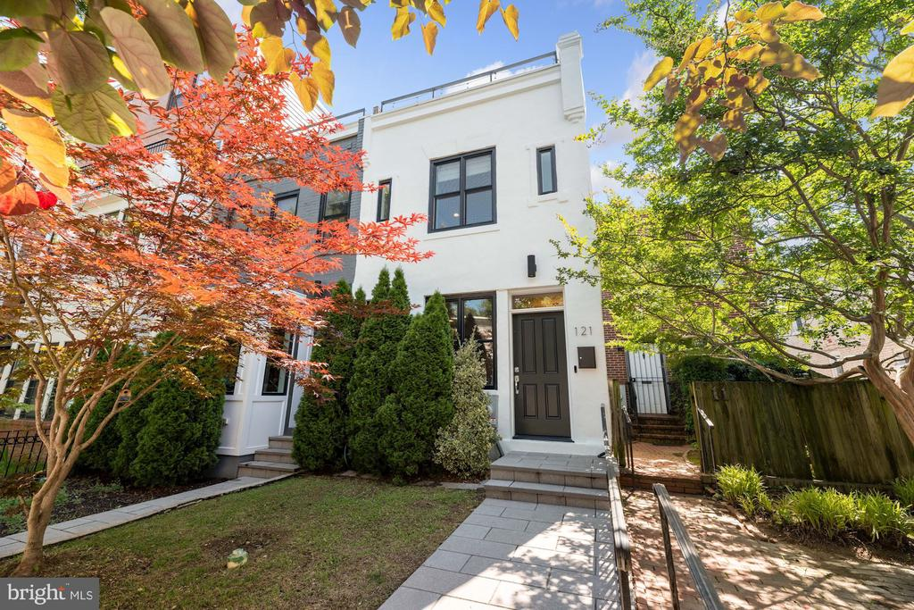 NEW LISTING!  OPEN Sunday, June 20th from 1 -3 PM! Originally built in 1900, this spectacular townhome underwent a complete renovation in 2015, marrying the modernity of the interior with historic and charming Capitol Hill. Filled with light and spread over three floors, this home feature stylish modern finishes throughout such as hardwood floors, floor-to-ceiling windows, custom built-ins and soaring ceilings. The main level features a completely open floor plan, with the living room flowing into the dining area which seamlessly connects with the chef's caliber kitchen. With an oversized island/breakfast bar as the focal point, the kitchen boasts high- end stainless steel appliances, gleaming white solid surface countertops and high-end cabinetry. Just beyond the kitchen is a secondary living space, with direct access to the first of two private outdoor spaces, which features a deck, spacious backyard and oversized, secure one car parking. The second level features two generously sized bedrooms. One being the first primary suite with a full en-suite bath and walk-in closet. A well-appointed full bath and laundry in the hall finish out the level. The third floor includes the second luxurious primary suite with 12-foot ceilings and custom closets. The en-suite primary bath has dual vanities, a glass-enclosed shower and generous amount of storage space. This level opens to a huge bonus room, perfect for a den, home office or gym, just to name a few. The room also has direct access to the second private outdoor space - a spacious roof deck perfect for entertaining and outdoor living, complete with electricity, a hard line gas hook up and picturesque neighborhood views. Located in the tree-lined, highly sought-after Capitol Hill, this townhome lives like a detached home, with its generously sized rooms and high ceilings. Walking distance to RFK and two-blocks from Lincoln Park, this thoughtfully designed home is not to be missed!
