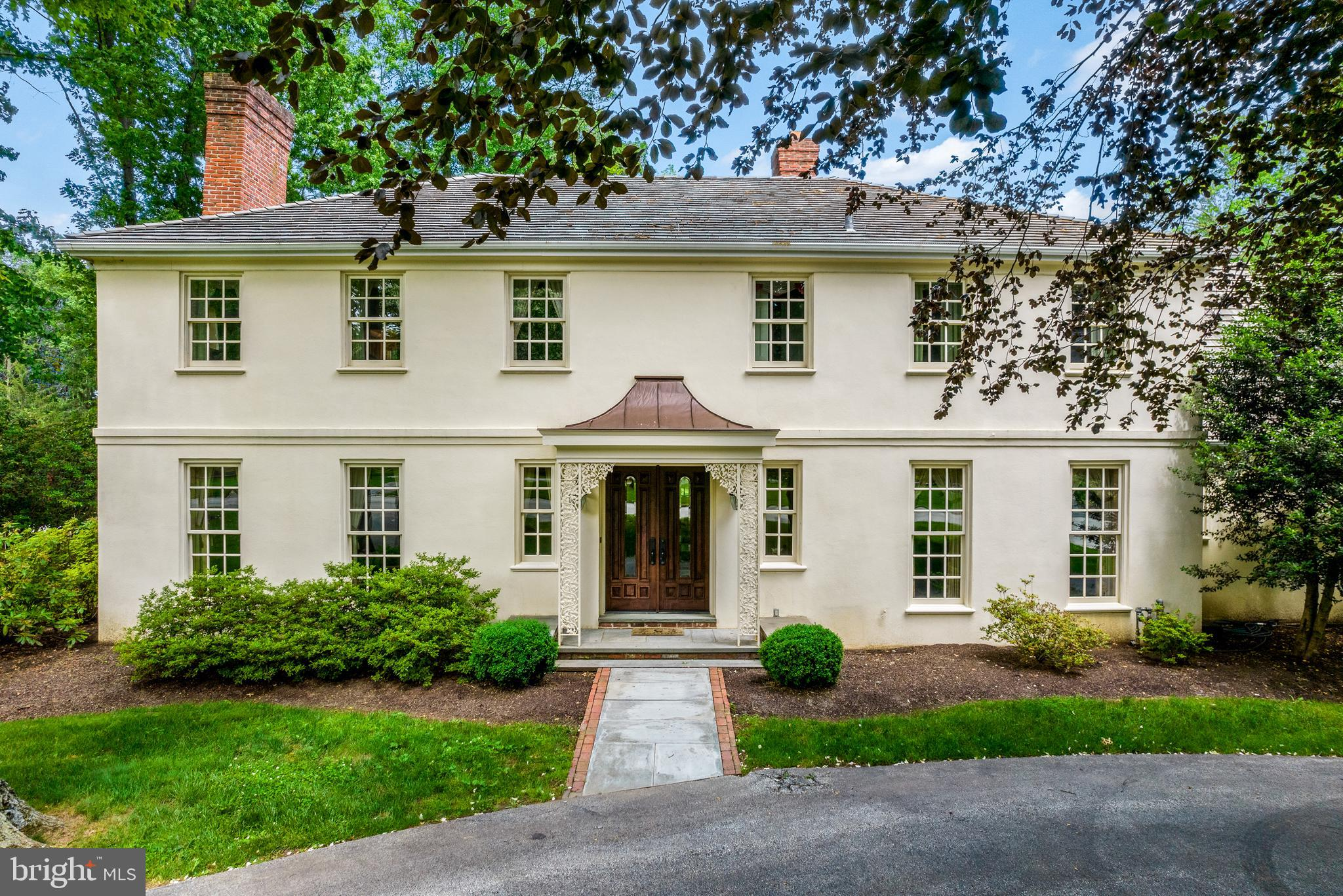 This lovely 4 bedroom 4 ½ bath Main Line classic Colonial is located on the premier north side of Bryn Mawr in the renowned Lower Merion school district, just minutes from Gladwyne, Bryn Mawr, Villanova and Philadelphia Country Club.  Major corridors to King of Prussia and center city Philadelphia are also conveniently accessible from this desirable location!    Situated on a magnificent corner lot along a secluded cul-de-sac, this property offers the ultimate in privacy!   The home has a newer cedar-shake roof and has been meticulously maintained.  It offers beautifully landscaped grounds with many species of mature trees, flowering shrubs and perennials that surround custom designed, flagstone and brick patios.  The large back yard is bordered by an expansive woodland area.  Enter the home through double mahogany doors into a foyer with a winding staircase, powder room and walk-in coat closet. To the left is a formal living room with wood-burning fireplace.  On the right, French doors lead to a formal dining room.  Beautiful hardwood floors extend throughout the main level.  The large kitchen offers granite countertops, a center island, imported tile floors and an eat-in dining area, with direct access to the back yard and formal dining room.  Also off the kitchen are the laundry room with built-in cabinets, two-car garage with built-in storage shelves and a second stairway leading to the upper level.   The main level also consists of a sitting room with a gas fireplace surrounded by beautiful millwork and built-ins, which opens to a great room with expansive views on all three sides.  The great room also boasts intricate millwork, built-in shelving, and a wet bar with a copper sink.  French doors lead to the flagstone and brick patios, perfect for entertaining!  The second level consists of a master bedroom with a fireplace, walk-in closets, and En-suite bath with a jetted tub, vanity, double sink, walk-in shower and heat lamps.  The upstairs landing includes a l