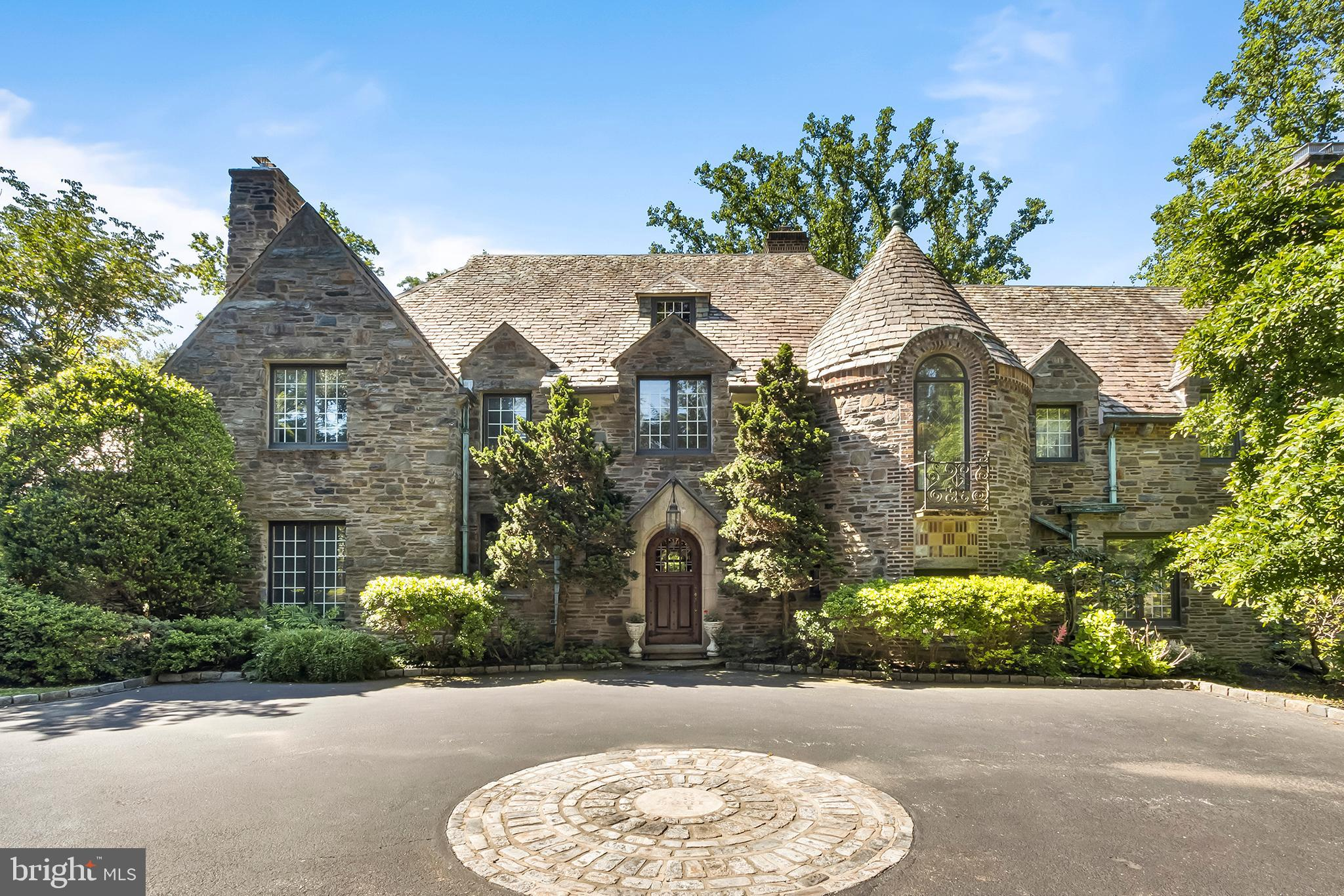 $600,000 PRICE REDUCTION. Now listed BELOW APPRAISED VALUE. You will definitely want to take a look at this unique property and take advantage of this rare opportunity. This stunning French Norman estate complete with a pool and tennis court displays the true elegance of a bygone era dating back to 1928. The unsurpassed craftsmanship and detail are evident from the moment one enters the courtyard. This spectacular home, situated in the heart of the Main Line, is on 2 plus acres and boasts a 4-car garage, multiple terraces, a koi pond, and everything needed for elaborate entertaining. Upon entering you are welcomed by high ceilings, exquisite moldings, stone and woodwork rarely seen in today's marketplace. It has been elegantly designed to incorporate both large and small spaces for intimate entertaining as well as larger more formal occasions.  As you enter the Great Hall with its exquisite wood paneling and built-in shelving you are welcomed with a fireside Sitting Area or Cardroom. This leads through arched doorways to an elegant Solarium overlooking multi-tiered terraces and the pool. There is a step-down Living Room enhanced by a stately stone fireplace, a high tray ceiling with a center rosette medallion, and large leaded glass windows with decorative transoms.  The quiet Study also features a private wet bar and window seat. A large formal Dining Room with an elegant triple window overlooks the pool and terrace area as well.  The Great Room is luxurious yet comfortable with a working bar for entertaining also featuring built-in shelves and cabinetry. The Eat-In Kitchen and service pantry is well equipped to host larger parties as well as everyday meals. There is an additional washer and dryer for excess linens and access to the attached 4 car garage.  The second floor has a gracious main bedroom with tray ceiling His and Her private Baths and Dressing Rooms with custom cabinetry. There are 4 additional bedroom suites. with custom bult-ins. There is private acc