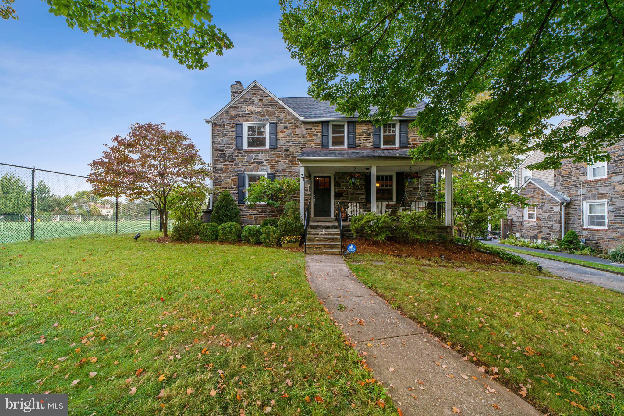 Gorgeous stone Colonial in the most popular neighborhood in Bala Cynwyd! As you approach the house, you'll find an inviting covered porch, perfect for relaxing and chatting with neighbors and friends as they pass by, on an evening stroll, heading to the athletic fields, or a visit to the free library on the front lawn. This street has a genuine neighborhood feel. Upon entering, you'll notice the hardwood oak floors and convenient drop space. The living room features a lovely fireplace and lots of natural light with a view of the open athletic fields (as opposed to another house) out the windows that also feature custom top-down bottom-up shades. Recessed lighting and tasteful media cabinets, which are included, make the best use of the space. Across the center hallway is a large dining room. The living room opens to a back corridor with access to the updated powder room, basement, hall closet and kitchen. The well-designed kitchen accommodates a comfortable eat-in area with a built-in storage bench. Soapstone counters, a Delta Touch faucet, high-end stainless steel appliances (Jenn-Air, Bosch, Frigidaire) and tumbled marble backsplash with black, white and gray palette—no updating needed in the kitchen! The back door leads to brand new flagstone steps down to driveway garage as well as back yard that borders expansive athletic fields complemented by landscaping that features year-round appeal. Upstairs are four generous bedrooms and two updated full baths. The rear bedroom provides access to a spacious roof deck with a unique private feel, featuring unobstructed, picturesque views of the sunset. The second floor includes ample closet space. Walk-up access to a large, floored attic offers plenty of additional storage . Down in the basement, you'll find a beautiful finished space including a private office with a window and a large open living space with a newer half bath. The mini-split unit here guarantees comfort in every season. A wall of built-in white cabinetry 
