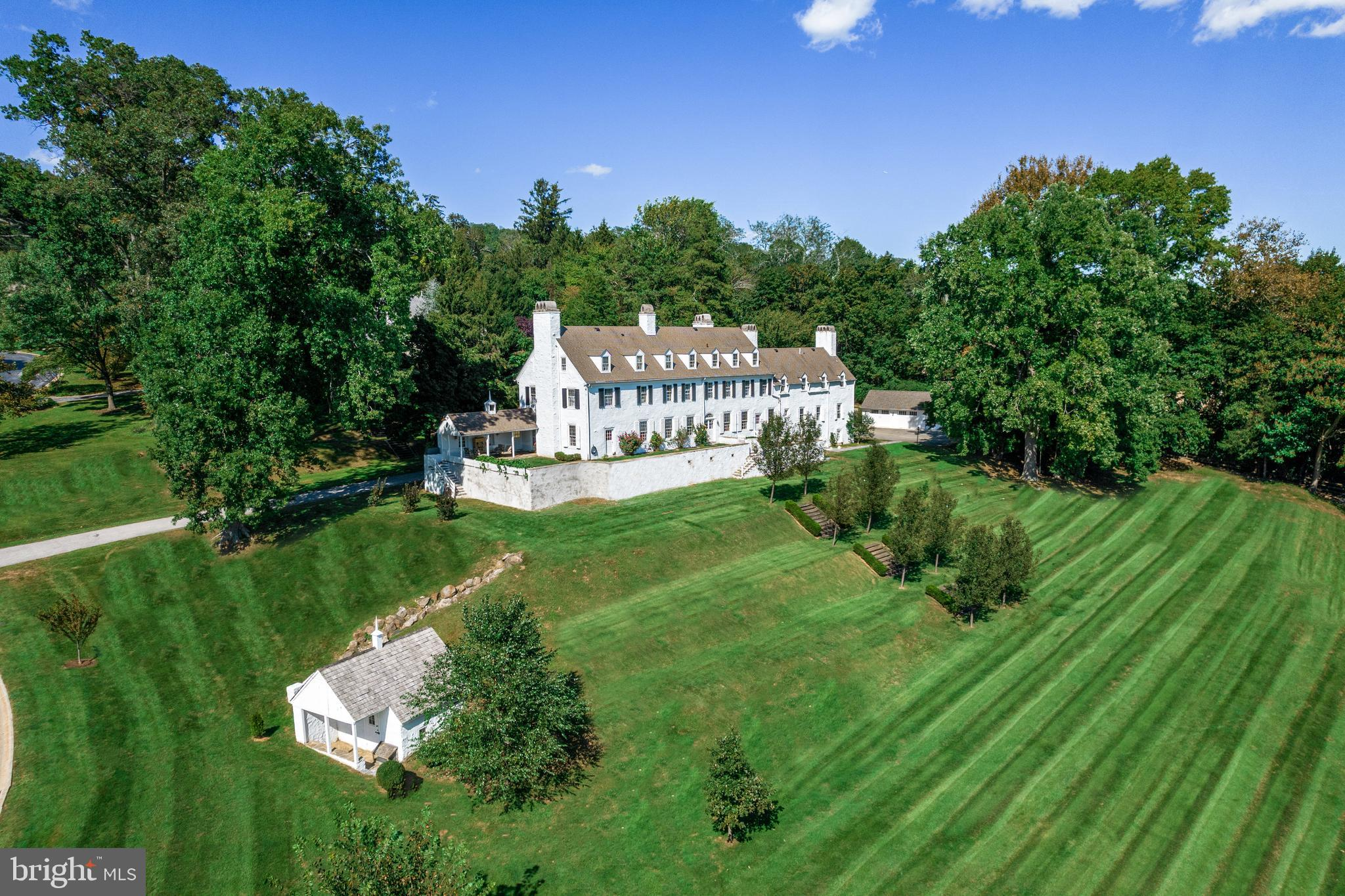 This meticulously updated Colonial Revival gem originally built in the late 18th century and expanded in 1927 by renowned architect R. Brognard Okie is set on a breathtaking 2.5-acre private lot with a terraced lawn and endless views of Gulph Creek and beyond.  Formerly the manor house of Woodstock, the Van Pelt estate at Radnor, it offers over 8000 square feet of living space above grade, complete with the original features installed by Okie, plaster on stone construction, eighteen-inch-thick stone walls, solid wood shutters, root cellar, spring house, and a recently built oversized 4-car garage.  With over 100 feet of linear southern exposure, the home boasts gracious sun-filled rooms that flow seamlessly into one another, perfect for entertaining, each space offering large deep-set windows, with two sets of French doors and four additional 16-lite doors leading to multiple terraces and extensive views.  High ceilings, beautifully restored original random width pegged floors, incredible millwork, 11 dramatic fireplaces, solid wood interior doors, wrought iron hardware, stunning craftsmanship including Okie designed built-ins and customized expanded spaces throughout the residence hint at the grandeur of yesteryear but perfectly suit today's lifestyles.  Recent improvements by the current owners include updated systems, plumbing, HVAC and electric.  On the ground floor, you will find an entry suitable for welcoming guests in the style of a by-gone era, a cavernous view of the handcrafted three-story staircase, a powder room, generously sized game room, dining hall with formal lounge, and a fabulously renovated gourmet kitchen with enormous walk-in pantry and service staircase.  From the formal entry, ascend the main staircase to a landing area complete with French doors to the library and four separate custom suites.  The primary suite occupies the west wing and offers privacy from the remaining rooms, with a newly renovated luxuriously appointed bath and walk-in d