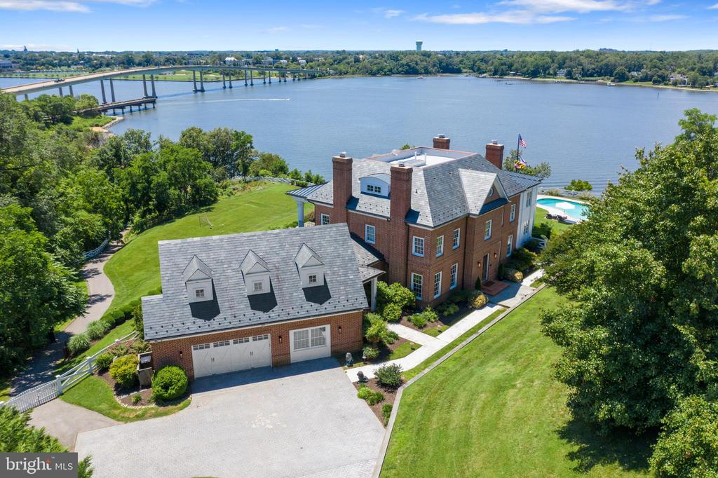 """A Stunning transformation! This iconic Annapolis waterfront estate has been meticulously updated with no detail overlooked.  Built in the Coastal-Tidewater style, this home was crafted to capture the commanding views of the Severn River and beyond.  The brick exterior and dramatic, formal columns add to the grand appeal of the home.  New heart of pine flooring with a light pickled oak finish was installed throughout the entire home lending a """"sea- side Hamptons"""" vibe to the interior. A grand, mahogany staircase welcomes you in the front entry hall. To the left of the front hall is a formal dining room and to the right is the study.  Each room is entered through french doors and has a wood burning fireplace with custom carved marble mantle.  The kitchen is a chef's delight. Thoughtfully laid out and outfitted with viking appliances, it is a true gathering space.  The oversized, soapstone island allows guests to mingle and chat up the host while enjoying the views.  A custom, hand-cut, subway tile laid in a herringbone pattern is a dramatic accent behind the custom hood vent and viking 6 burner range.  A farm sink, dual dish washers, ice maker, warming drawer, pot filler and custom rattan-basket globes complete the """"must haves"""" of any high end designer kitchen. Moving down from the kitchen is the family room with two-sided, wood burning fireplace with custom, hand carved marble mantle.    On the other side of the two way fireplace is what the owners affectionately refer to as 'The River Room.' A comfortable yet elegant space with panoramic views of the Severn River and swimming pool, a full bar with beverage fridge and sink, a full bath also accessed from the pool deck through a set of custom wood, exterior doors.  On level two you will be greeted by a set of french doors opening to the second level lounge and game room...or whatever you wish the room to be...including a bedroom.  This room has its own balcony with incredible views and full bath.  To the end of the ha"""
