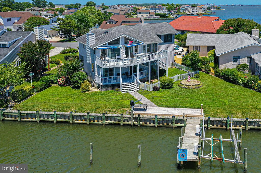 """Make family memories here!   This is the one you have been waiting for.  A partially furnished elevated four-bedroom two bath, two car garage (approx. 22x22) waterfront home built for view. This home is in the cull de sac of Wood Duck Dr. with breath taking water views.  Water views from all bedrooms, 2nd floor living area, kitchen, separate dining room and Ocean City skyline views from a step up to the media/family gathering room (approx. 400 sq. ft). The Kitchen has been recently remodeled with granite counters providing additional seating, cabinets, microwave, stove and dishwasher.  This home features a 25 ft. pier with boat lift in addition to a personal craft davit and 125 ft. of  bulkhead providing access to the open waters.  The bulkhead was replaced about three years ago.  There are two waterfront decks for you to sit, relax, and enjoy the wonderful views and bay breezes.  Decks leading off the home have a separate stair to a large, cleared back yard with a partially fenced in area for children or a family pup.  Two gas fireplaces, one double sided in the dining room and office room or sitting room off the main bedroom for cozy evenings.  An additional fireplace located in the living area off the kitchen. Two attached storage sheds for storing boating/yard items. Pull down stairs in home provide access to the floored attic and also separate garage access for additional storage. Lennox forced air furnace with cooling unit. Separate ductless unit for family/media room.  Navien tankless water heater.  Roof is approx.. 10 years old.   Home is being sold """"As IS"""""""