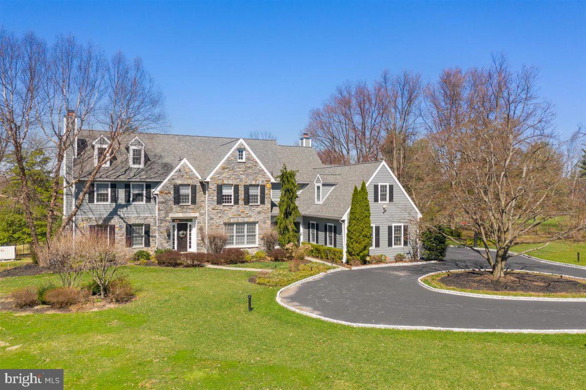 Sitting on 2.65 bucolic acres, completely fenced-in,  this 6 Bedroom 7 Full bath, and 2 Powder rooms home is on one of Gladwyne's most desirable streets. Enter through secure gates onto a circular drive with professional landscaping and hardscaping, including the cobblestone curbing. The main entrance welcomes you into a large bright center hall foyer with hardwood floors that flow throughout the home. The French doors to the rear of the foyer lead to the newly updated flagstone deck and resurfaced pool and spa. Directly to the left of the main door, you'll find the living room including a gas fireplace, perfect for entertaining friends and family. The first-floor office features floor-to-ceiling bookcases surrounding the entire room. There is a formal dining room large enough for any size holiday dinner party.  The kitchen with a beautiful breakfast room is large and bright and full of white cabinets, a walk-in pantry, stainless appliances, and an extra-large seated island to encourage gatherings in the kitchen. The kitchen flows effortlessly into the family room with a cathedral ceiling where you will enjoy detailed molding and built-ins encasing the gas fireplace, accentuating the warm and cozy vibe of this home.  The walls of glass windows allow you to enjoy the breathtaking views of the private grounds, with sliding doors to access the expansive flagstone patios. Ascend to the second level from the foyer or the rear stairs to the primary suite with a luxurious, resort-like bathroom with heated flooring, a soaking tub, glass-encased shower stall with dual shower heads, double vanity sink, and two walk-in closets. Three additional bedrooms on the second level, each with an en-suite bathroom including heated floors. The third floor is a recently finished loft space with a half bathroom. The sixth bedroom is located on the main level of the home with an easily accessible en-suite full-bathroom designed for Persons with disabilities. On the fully furnished lower lev
