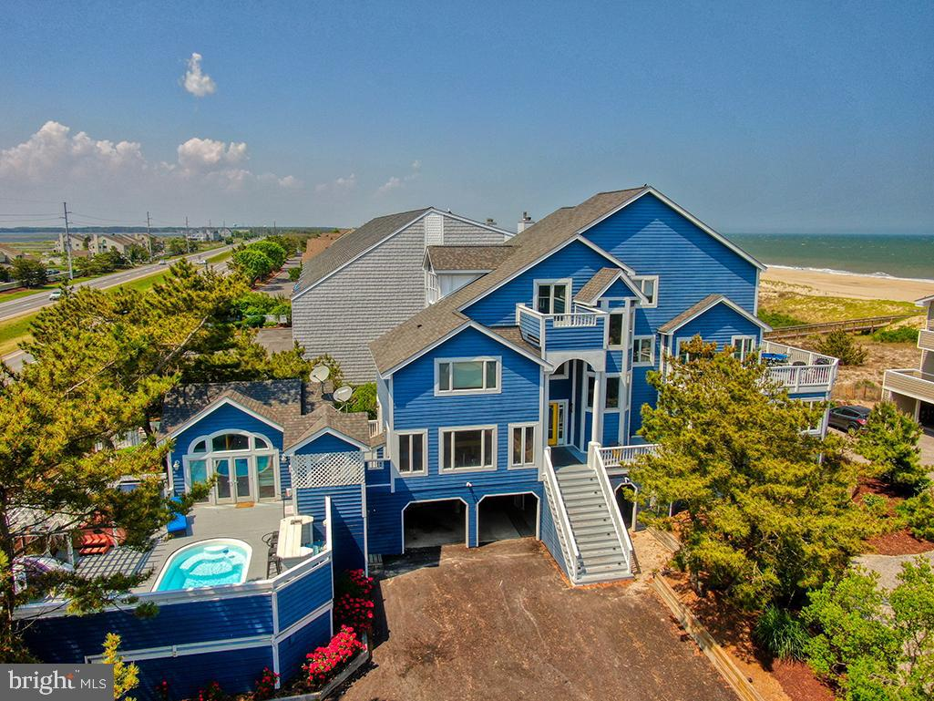 """This exquisite beach home gives new meaning to """"ONE OF A KIND! It is located in an enclave of 6 very private estate homes  that are all oceanfront and or ocean view. This home features 7 bedrooms and a private pool with a cabana house. The cabana house can also be used as a private small apartment;  it includes a kitchen , full bath and sleeping area. There is no need to pay oceanfront pricing when you can be just steps to the ocean and enjoy both bay front sunsets and ocean front views. The premium placement of the home allows beautiful ocean views.  The home offers a large dining area, gourmet kitchen, several addition eating areas and 3 decks to be away from it all and enjoy the soothing sounds of the ocean and warm sunsets of the bay. There is an inordinate amount of sleeping space and bedrooms...the home is a """"cash cow""""!!!! The 2021 rental income has exceeded $201,000; upcoming rentals for 2021 should exceed $220,000.  It continues to increase as the rates increase and the demand exceeds a full Summer, both shoulder seasons, holiday weekends and almost everything in between.  For any investment buyers, this is a great location, amazing return on your dollar and an opportunity to own a """"ONE OF A KIND"""" beach home. Rentals are being booked for 2022 and are filling up...buy this house and immediately have cash flow...year round!"""
