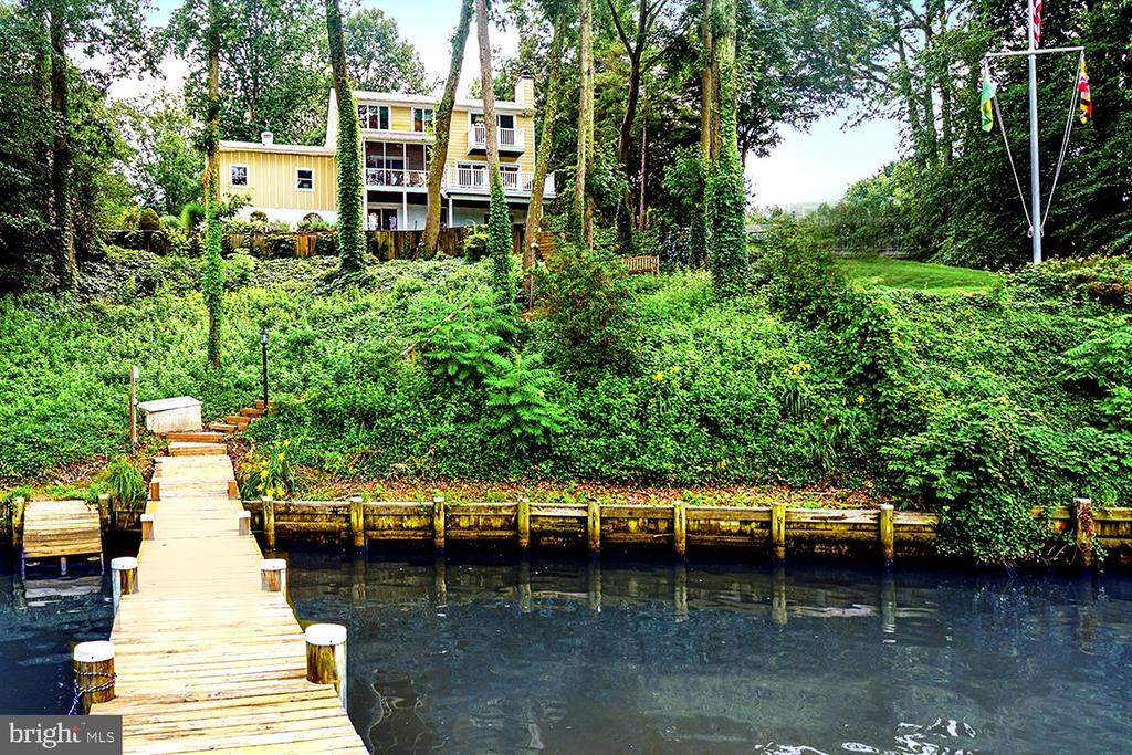HUGE PRICE REDUCTION!! PRIVATE COLONIAL PERCHED ABOVE MAGOTHY RIVER COVE  !  TOTAL SERENITY on protected Mill Creek opening to the Magothy with direct boater's access to the Bay  !  Pier w/lift, jet ski lift & floating dock  .  Boat to THE POINT Restaurant for crab cakes  !  Bask in Twin Harbor amenities including boat ramp, picnic pavilion, beach & playground  !    Custom updated home maximizing light &  water views  .  Waterside screened porch & deck for sun and moonlight dining  !  Masterful interior detailing with rich hardwoods, custom built-ins, and designer wall treatments (BR with tie dye walls!)  .  Creek view Living Room sharing fireplace ambiance with Dining Room, both with sliders to the outdoors  .  Den with built-in bookcases  .  High-end granite/stainless chef's Kitchen  .  Primary Bedroom haven with fireplace, water view balcony, Hollywood dressing Room, enviable walk-in closet and ensuite spa Bath  .    Two additional Bedrooms & hall Bath with distinctive personality  !  Lower level with Family Room walk-out to waterfront patio, and BR/BA (possible In-Law Suite)  .  Multi-vehicle parking court & 2-car garage  .   Commuter convenient to RTs 50/2/97  .  YOU WILL BE COMPLETELY CAPTIVATED!
