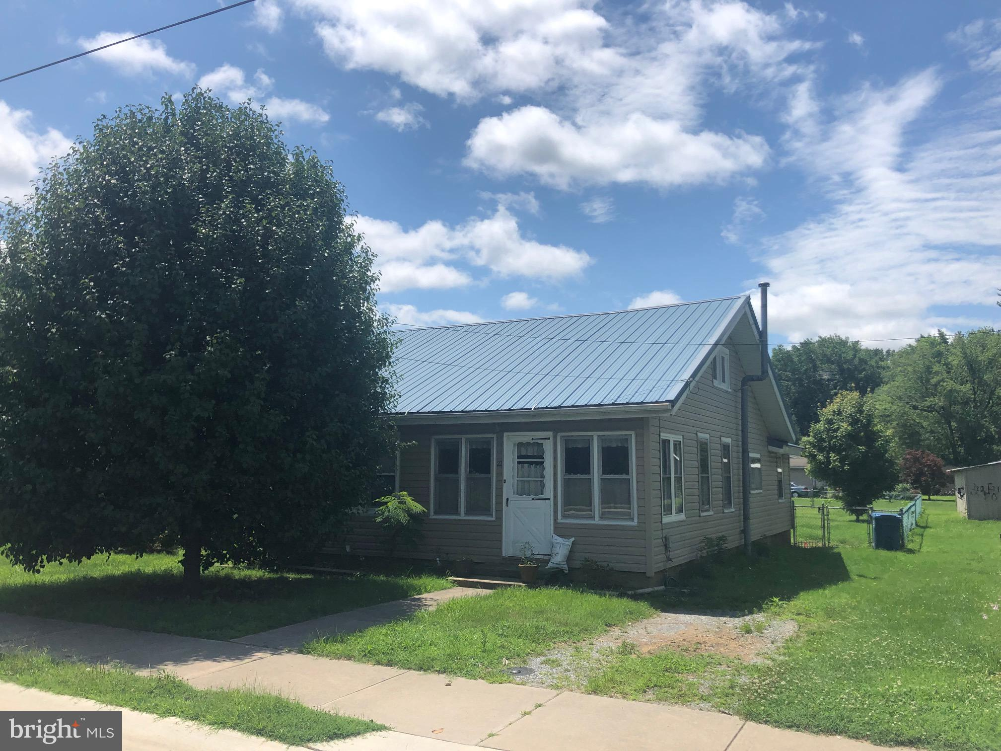 This is a charming in town find.   Sold As Is.... this home has a fenced in back yard, vinyl siding and a metal roof.  The kitchen has a refrigerator and stove. Hardwood floors along with some carpet.  Easy to show, this won't last long