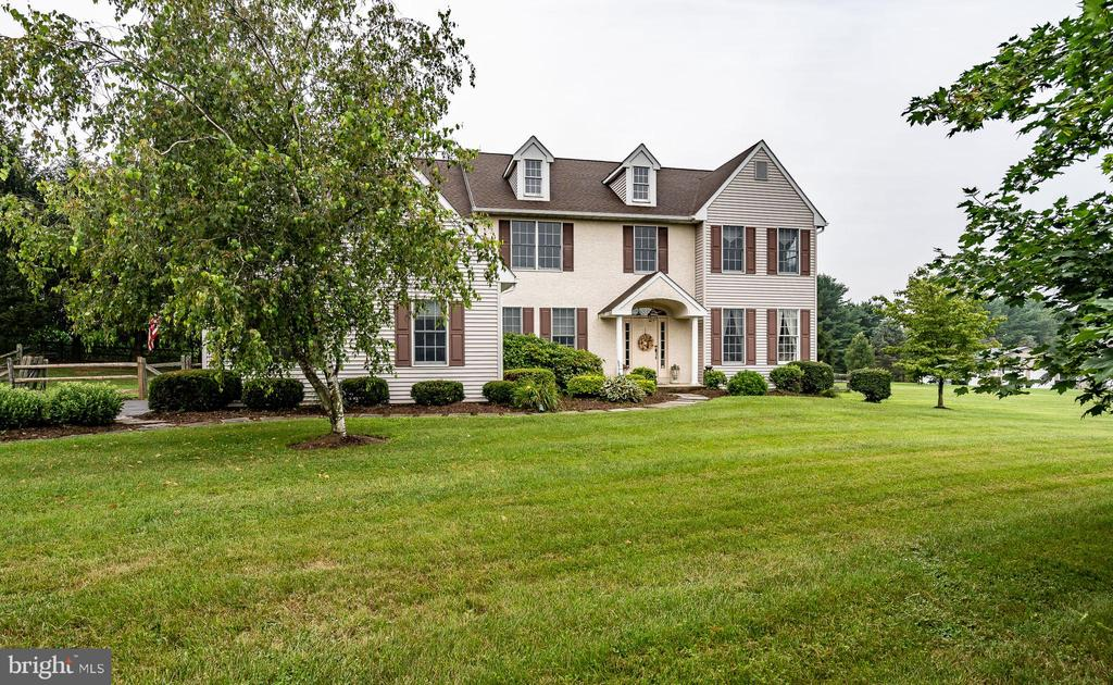 """This gracious Colonial, in a lovely pastoral setting, has just over an acre of level, very private land backing to mature trees and cornfields. Yet this piece of idyllic countryside is remarkably close to all of Chester County's main thoroughfares and destinations, including being part of the award-winning Downingtown school district. The dramatic two-story hardwood foyer with a turned staircase gives a five-star first impression.   Opening to the right is a spacious formal living room with built-ins and to the left the welcome, and highly sought-after, feature of a home office. A formal dining room has hardwood floors, chair rail, crown molding and will comfortably accommodate seating for everyone on your special occasion guest list. The gourmet kitchen has been totally remodeled and upgraded with granite counters, an artfully coordinated backsplash, a double sink, stainless steel appliances, a center island, plentiful cherry cabinets, and a large pantry. Its breakfast room overlooks the back patio and yard by way of a large double glass sliding door -- a view that says """"it's going to be a great day!"""" The adjacent family room is spectacular -- two stories in height, floor-to-ceiling stacked stone fireplace, a convenient back staircase, and walls of windows all combine to make this room bright, airy, open, and certain to be a favorite family gathering place. A half bath and laundry room, with soaking tub and access both to the backyard and the two-car garage, finish out the main level.   Upstairs, all newly carpeted in 2021, the primary bedroom is a luxurious suite, featuring a large sitting room, 9' tray ceiling, walk-in closet, and spa-like en suite bath, complete with a jetted bathtub. Three additional bedrooms and one full bath complete the second level. The basement has been fully finished and offers plentiful options for recreation, workout space, media, hobbies, and tons of storage.   The outdoor living space is another exceptional feature of this home. Matur"""