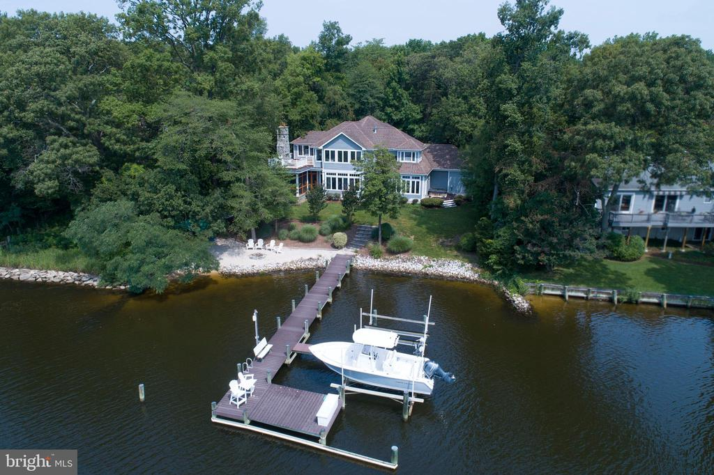 Spectacular and unique Magothy River waterfront home which has been masterfully updated, top to bottom. Located in one of Severna Park's best-kept secret communities of Cape McKinsey, without a mandatory HOA fee! The home has been completely renovated since the owners purchased it in 2004. Step inside through the 2-story foyer to the main level, boasting natural light and finished hardwood flooring. The gourmet kitchen opens to the family room, situated along a wall of large windows that face the water to capitalize on the incredible views. The screened porch provides an entertainer's dream of indoor/outdoor dining and living, accompanied by a large stone fireplace and waterfront views, offering direct access through the kitchen or family room. There is a separate room facing the water on the main level, which can be used as a bedroom, home office, or entertainment area. The master bedroom features an impressive upper-level deck, with a fully functioning stone fireplace, outstanding views of the water, and a spiral staircase to the backyard. This home has its own beach and dock, hot tub on the rear deck, and large tiki bar - your own private resort right at home! A discerning water-oriented buyer will LOVE the water-frontage of this home as it combines a true boater's needs and area for a relaxing sunrise OR sunset to watch off the pier or rooftop deck. The pier has a boat lift and is located inside the no-wake zone making this the perfect spot for boating enthusiasts. It is incredibly difficult to find a waterfront home in a good community that has been updated, with a spacious backyard, and incredible waterfront access. Look no further....this turnkey, waterfront home is truly one of a kind!