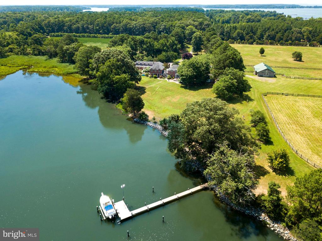Wonderful 51.5 acre waterfront estate in prime location between Easton and St. Michaels.  Just 75 minutes from BWI airport ,1 1/2 hr from D.C. and Baltimore, and 3 hr from NY. Property offers complete privacy and extends from Pea Neck Rd to Folly's Cove Rd. Roughly 35 acres are currently tilled and the remaining are in pasture and around the house. Beautiful entrance with circular drive leads you to the French/federal style brick home whose interior boasts 4 BR/4.5 BA. Great views of Folly's Cove and the property can be seen from all rooms including the renovated kitchen and comfortable family room.  The master bedroom with it's high ceilings, sumptuous bath, and large deck were added by the current owners and has it's own private stairs.  A gorgeous brick breezeway with pretty formal garden connects the 3 car garage with full 2 BR guest apartment above.  Multiple rooms attached to the garage include large workshop, office space, possible art studio, and more. The protected pier has been re-decked with new stringers in 2021 and has an electric lift and 3'MLW. The shoreline is rip-rapped and the cove offers sanctuary to many species of wildlife. In addition there are 2 large ponds which make this a hunter's/wildlife enthusiast's paradise.  The large Morton barn includes 5 stalls, feed room, wash stall, tack room, and large hay loft. 5 fenced pastures (1 with a turn out shed) are conveniently accessible.  Adjacent are 2 sheds offering  equipment storage plus a large greenhouse. There is also room for a waterside pool. No further sub-division of parcel is possible.
