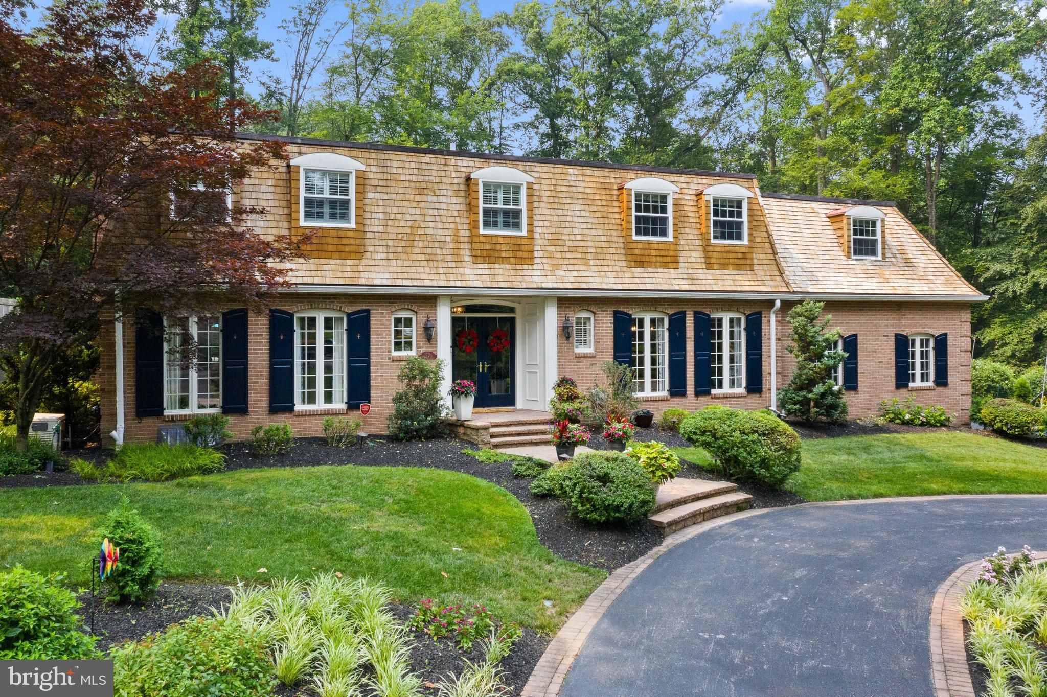 Move right into this traditional 2 story colonial in Wayne's Northwoods neighborhood! This home has a wonderful interior and exterior flow and plenty of updates! The first floor has an inviting Center Hall, bright Living Room, sizeable Home Office, gracious Dining Room, and Half Bath. The epicenter of the home is the open Kitchen, Family Room, and Breakfast Room area that overlooks and accesses the private backyard. The Kitchen has a large island (with seating and a wine fridge), top-of-the-line appliances, and custom cabinetry. The Family Room has a fireplace, a built-in bar area, and custom architectural touches. The Breakfast Room has a vaulted ceiling and is bathed in light. A long hallway off the Kitchen offers a pantry, more cabinetry, garage access door, laundry center, and an exit to the driveway. The entire first floor has beautiful hardwood floors. Upstairs, the Primary Bedroom Suite has a completely redesigned closet system and a renovated Primary Bath.  Down the hall is a large bedroom that has a built-in window seat and cabinetry, and a completely updated bathroom, and a private staircase to the first floor. There are two additional Bedrooms that have closet systems and custom built-in window seats. A fifth upstairs Room also has two built-in window seats and is used currently as a Guest Room (the closet is home to the new HVAC system.) A spacious Hall Bath with double sinks and bathtub complete this level.  The finished area of the basement has 2 lounge areas for TV viewing, an exercise room, and a gathering table/refrigerator area that make entertaining easy.   The exterior is professionally landscaped and has extensive hardscaping. The front yard is showcased by a circular driveway offering a dramatic entrance to the double glass front doors of the home. Additional parking is available on a side driveway that leads to a two-car garage. In the rear of the property, a Trex deck runs the width of the back of the house and can be accessed from the Living