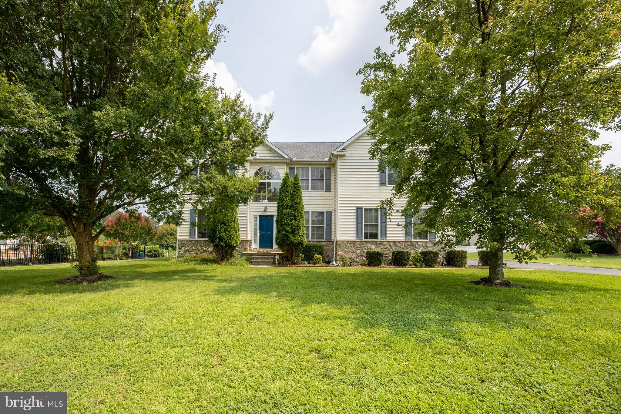 A high caliber home in Country Fields! This 2005-built, 4BRs/2 ½ bath traditional home boasts almost 3,500 sq. ft. of space and is nestled on over ½ acre with quiet countryside as backdrop to peaceful living. Mature trees dot lush, level front lawn that precedes this stately white siding edged with Williamsburg blue shutters/front door with stone skirt 2-story home, while low-lying hedges hug sidewalk and tall, cone-shaped pines mark open, elevated, sun-splash front entry. Home's updates include new irrigation system powered by new 4-inch well (2021), new dual-zone AC (2020), and new primary bathroom shower. Step inside to luxury! Palladian window adds beauty and natural light that spills onto warm, polished hardwood floors in buttercream painted, cathedral ceiling foyer. Balcony overlook is just above and adds elegance to already regal entry and first impressions measure high when recognizing front of home is comprised of formal rooms. To left is LR, where hardwoods turn to soft, neutral carpeting and together dual window and single window provide corner of abundant natural light. Relax in here with pre-dinner drinks and post-dinner dessert! Opposite LR and across foyer sits DR, where neutral carpeting is repeated, and lovely chair rail is added. This formal space is the base of entertaining! With FR, modern architecture emerges with high ceilings, different height windows and an airiness that permeates the room. This notch-above 2-story FR offers twice the ambiance with striking dual-level windows, prominent, exposed, carpeted staircase and sweeping space to live life! Collection of couches, chairs, coffee table and comfortable furnishings make this the leading laid-back locale for go-to gatherings and everyday relaxing! Sweeping kitchen is filled-to-the-brim with personality! Ceramic tile anchors floor, while pristine white cabinets accented with silver hardware are paired with white appliances including high-end refrigerator/freezer. Blue trim, echoed from home'