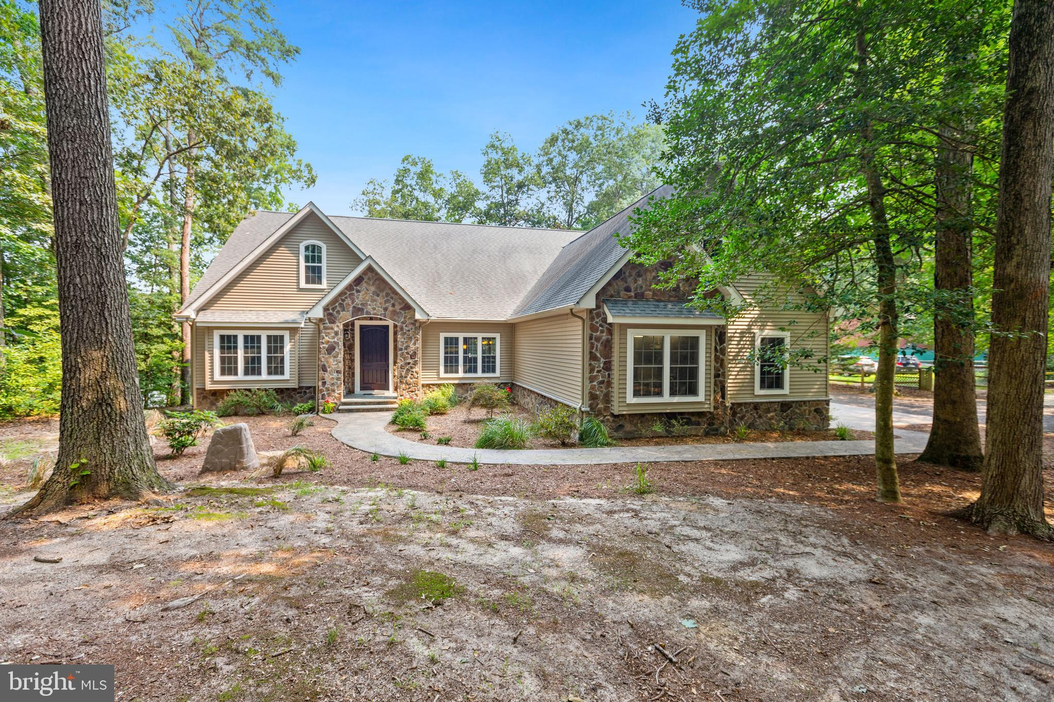 This one-of-a-kind, contemporary, 2-story ranch home is nestled on a private wooded paradise along the banks of the Nanticoke River, and exceeds expectations! From the moment you arrive you are greeted in splendor with lush landscaping and custom hardscaping that leads you to the welcoming covered front porch. This stunning 5-bedroom, 4-bath home is sure to please, boasting premium upgrades throughout the foyer setting the tone for the detailed craftsman finishes, feature lighting, perfectly planned spaces, and designer touches that you will find throughout. Inside, the foyer graciously opens to exquisite interior spaces, designed for easy-living and grand-scale entertaining beginning with the elegant two-story living room with a floor to ceiling raised hearth fireplace, handsomely encased in stone, and stacked window views of the back deck and backyard oasis, and the stunning Nanticoke River! The gourmet kitchen is appointed with lovely sienna colored cabinetry, contrasted by light granite counters, a suite of stainless-steel appliances, a bi-level center island with breakfast bar, and highlighted with featured, recessed and under cabinet lighting. The kitchen is enhanced by a thoughtful floor plan that includes a very generous walk-in pantry, and is sided by a formal dining room, and a breakfast dining area with a walk-out to the deck. The main level owner's suite features a tray ceiling with custom fan, a wall of picture window views of the river, private access to the deck, and offers 2 sizable walk-in closets. The deluxe luxury ensuite offers two vanities separated by a stack of custom cabinets, a free-standing spa-like tub, grand-scale tile and glass enclosed shower stall, and a private water closet. Off the foyer on the main level, French doors open to the well-proportioned office with custom built-ins perfect for inspired work at home, but also has a closet and shares a full bath, so it could be another bedroom with ensuite on the main level. Two additional 