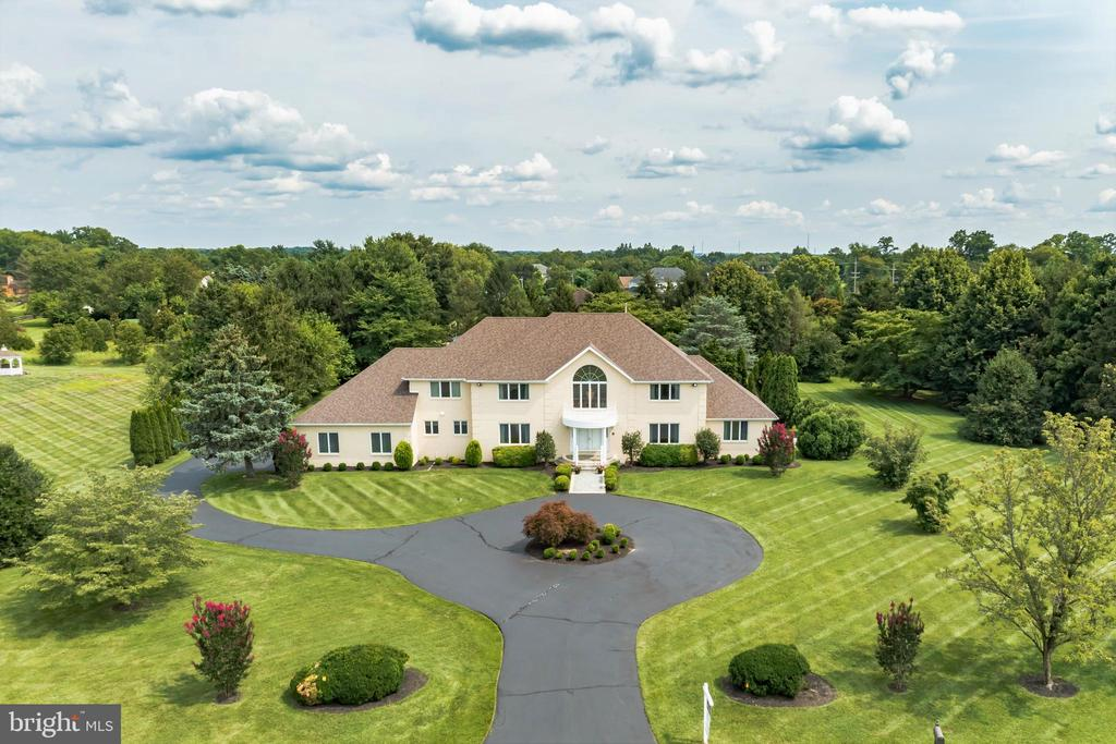 A TRULY RARE OFFERING IN THE PRESTIGIOUS COMMUNITY OF HARTFORD GLEN, BEAUTIFULLY SITUATED ON APPROX.  2 ACRES OF PRIVATE GROUNDS.  A circular drive elegantly welcomes you to this stately brick residence.  The two-story Foyer entrance, showered in natural sunlight, features a  distinctive palladian window, marble flooring, curved wood staircase, and is flanked by a formal Dining Room and Living Room with hardwood flooring.  The central area of the home showcases an open, flowing, and inviting floor plan with large windows overlooking the scenic grounds and swimming pool.    A striking Sun Room creates architectural interest and appreciation for the privacy of the backyard lined with mature trees. Gather in the spacious Kitchen while entertaining guests or in the Family Room around the gas fireplace.  A 2nd catering Kitchen can help make party preparation more convenient.  The main level also offers a Laundry Room, Powder Room, and In-Law/Au Pair Suite with full bath, bedroom, and Study or Sitting Room.    The main level full bath is accessible directly from the outdoor pool area.  All of the bedrooms on the upper level are generously sized with ample closet space.  The Owner's Suite with double door entrance offers 2/3 walk-in closets and en-suite bath.  Bedrooms 2 & 3 share a large private bath, while Bedrooms 4 & 5 share a hall bath.  The 4th bedroom features a fabulous suite with bonus/dressing room and walk in closet.  A sizable finished Lower Level awaits with sprawling recreation area, bonus rooms, wet bar, full bath, plus a tiled room for a potential kitchen.  A staircase walks up from the Lower Level to the 3 car oversized garage.   Relax on the patio and enjoy the heated swimming pool and tranquility of your own private sanctuary in an exquisite neighborhood.  The roof and hot water heater were recently replaced.  Located just minutes from major access routes to Philadelphia and NYC, Moorestown offers excellent schools, a picturesque downtown, distinguished 