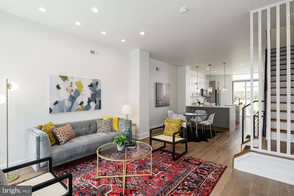 Luxury living at it's best in Norris Square! Welcome to 187 W Norris St. This stunning 2400+ square foot, new construction boasts an impressive amount of upgrades making this beauty a stand out in a sea of cookie-cutter properties. Forget narrow, dark row homes, this sun soaked property boasts oversized windows and plenty of room for entertaining and family living. Upon entering you're greeted with a modern wood door, 9ft ceilings, a unique accent wall and an open layout allowing for designated living and dining that flows naturally into the tasteful custom kitchen. No bland white cabinets here! The kitchen is a chef's dream with tall gray shaker cabinetry, black hardware, granite waterfall countertops, and black stainless appliances. Natural light floods the space from the huge sliding doors with transom window and the large kitchen island is perfect for casual dining or serious meal prep. A convenient half bath is tucked away off the kitchen, ideal for guests and indoor/outdoor entertaining. The private back patio has been finished with new wood fencing, pavers and a custom planter. String up the twinkle lights, get out your gardening gloves or uncork a cold bottle of rose. This space is just waiting for your special touch. Back inside the hardwood flooring continues upstairs to 2 bright, spacious bedrooms, one with it's own en-suite full bathroom and another full bathroom located in the hallway- a perfect layout for kids or guests. Up on the third floor the spacious primary suite has it all- a private balcony, massive walk-in closet with adjoining laundry room and an impressive, 5-star hotel-grade 4 piece bathroom. The en-suite spa-like bath with double sinks, glass enclosed shower and vessel soaking tub is a retreat like none other. The third floor also has a convenient bar area with an under counter ice maker and beverage cooler! Perfect for evening cocktails on the roof deck above. Up on the roof deck you'll enjoy city views and plenty of space to relax. Back 