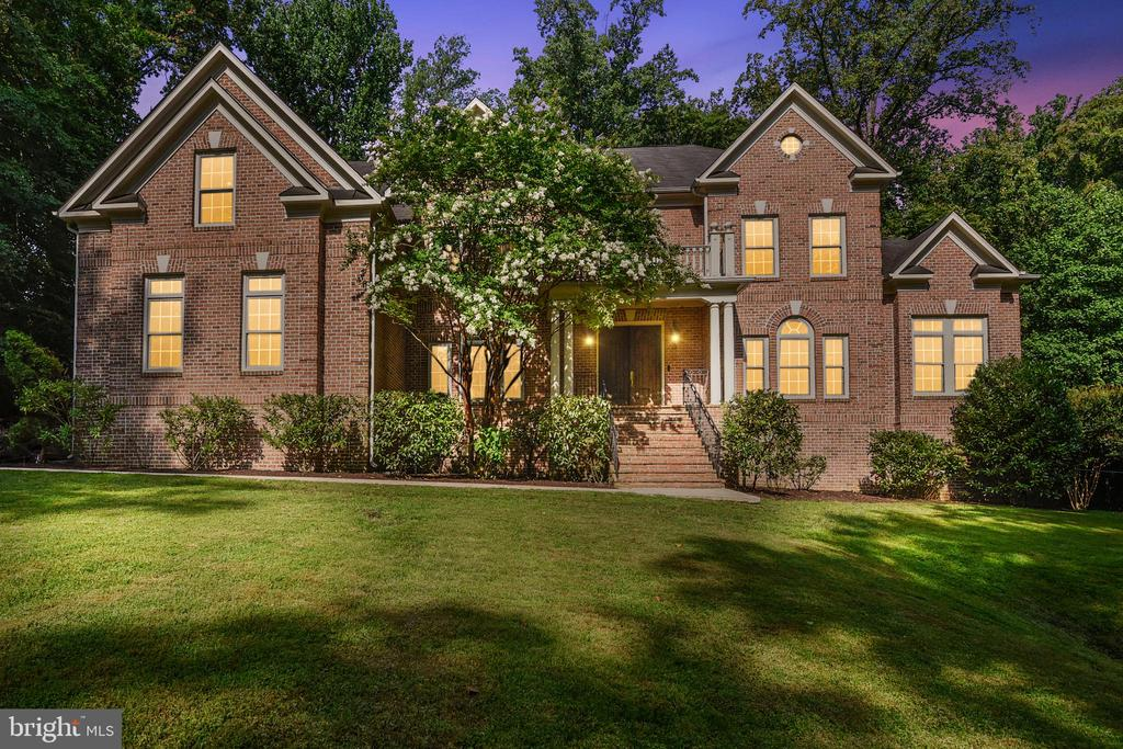 Travel down scenic, treelined Columbia Rd and you'll find this impressive estate home, set far back on its lot, where it awaits its new owner. Nearly an acre of mature trees and lush landscaping frame this custom brick home. The stately formal entry opens to a double height foyer where guests are greeted by a dramatic staircase featuring a custom wrought iron balustrade, and marble tile floor. Host intimate conversations and splendid gatherings alike within several irresistible living spaces all elevated by builder upgrades including architectural moldings, coffered and tray ceilings, palladian windows, and a stone clad fireplace ascending two floor heights. The dining room is perfect for holiday dinners while the enourmous sunroom is ideal for brunches and birthday parties. The two level family room and open kitchen make hosting a large group a breeze while the chef cooks up a storm on the high end appliances.  Add a perfect bar to create lots of happy memories. Bring your in-laws! They will not be relegated to the basement in this home because all five bedrooms are above grade including a bedroom with private full bath on the main level! In the principle suite, relax with your private fireplace or enjoy the cozy fire from the soaking tub and riverstone tile shower. Two large vanities make getting ready at the same time easy. And then there's the closet. Kylie Jenner couldn't fill this closet! The remaining three bedrooms are bright and spacious. New carpet just installed in all the upper level bedrooms. A three car garage with separate entrance so dirty clothes can be dropped at the laundry room which features LG Steam Washer and True Steam Dryer with a washtub. Use your imagination to finish the over 2000sqft of basement space with double width walk out to your lush back yard. Close to multiple parks including Mason District Off-Leash Dog park. 4min to 395. 3min to Little River Turnpike. 6min to 495 Home warranty included. Don't miss this one!