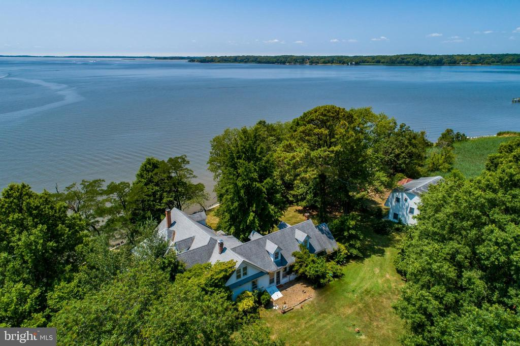 Stunning waterfront farm set on a peninsula on 30 acres in historic Chestertown, Maryland with spectacular views. Practically an island, the home is surrounded by rip rap,  pilings for what was a deep water pier & boat house with over 1,000 feet of white sandy beach. The channel is right next to the property allowing for beautiful close boat watching and easy access to deep water! The 1920's southern style home sits within 50 feet of the waters edge allowing views from almost every room. Connected to the home is a historic 1700's log cabin, one of the many that were  found on the property when the home was built. Just next to the home is a detached over-sized two car garage with living space above built in the late 90's where the water views never end! An open concept living area consists of a large kitchen , living/dining, full bath,  two bedrooms, hardwood floors and custom ceramic painted tiles. Following the cordery road along the waters edge is the enormous barn with multiple horse stalls. The farm land is leased to a farmer for the remainder of the season.
