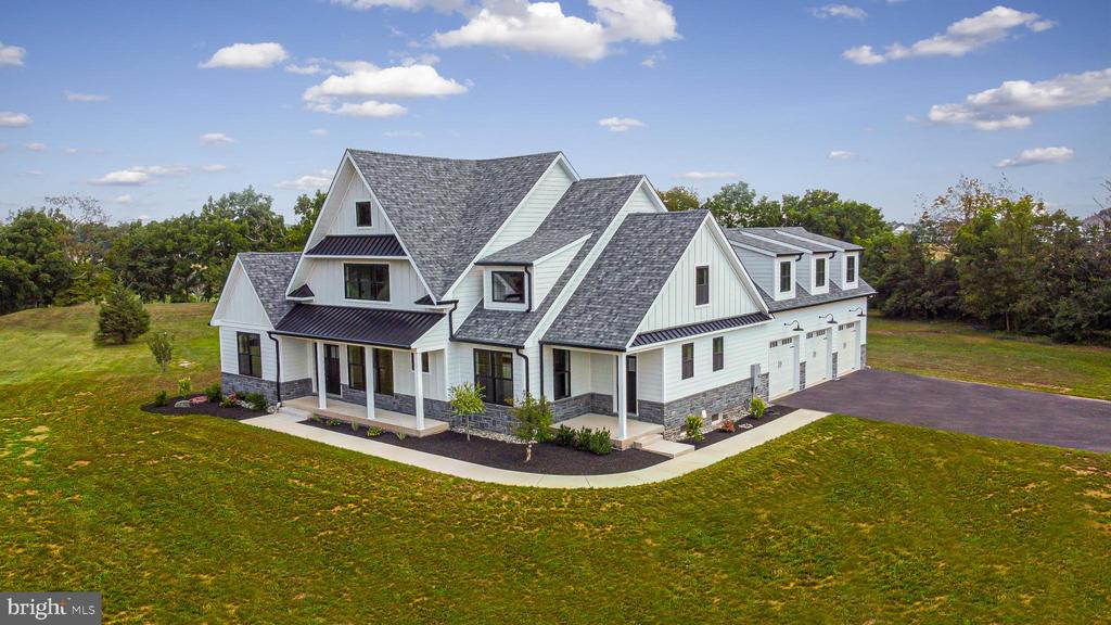 """Looking for your Farmhouse dream home!? Wait No Longer…. This Pugliese Brothers new build has the modern farmhouse style black and white theme carried inside and out situated on 2.5+/- acres. This FIRST FLOOR MASTER home features 4 bedrooms, 3.5 baths and a 3-car garage. Outside finishes include James Hardie Cement Siding, authentic stone veneer, oversized 5"""" black gutters and downspouts and black Anderson windows. Throughout most of the main level you will find stunning custom milled 6-inch-wide whiteoak flooring enhanced by the abundance of recessed and natural lighting with oversized black windows and doors, 9 feet tall ceilings with the open concept floor plan makes this perfect for entertaining. The main level features a generous family room open to the kitchen with a gas fireplace and custom built in cabinetry, dining area, first floor owners suite with walk-in closet and organizers, an ensuite bath with large freestanding soaking tub, and Carrara Marble shower complete with bench, niche, handheld and rain shower head, double bowl vanity and a wet bar tucked away leading into the master suite. The farmhouse style kitchen boasts quartz countertops, stainless steel Kitchenaid appliances, gas cooktop and pot filler, shaker style 42-inch-tall cabinets, a large center island complete with a farmhouse sink and enough room for up to six seats and a walk-in pantry. Entering the mudroom from the three-car garage and the side porch service door entrance you will find a natural black slate floor and custom-built bench seat along with shiplap wall accents, a laundry room and powder room! On the second level of the home, you will find three sizeable bedrooms, a jack and jill style full bath with double vanity, another private full bath, a separate loft/study area along with a massive bonus room over the garage perfect for a 5th bedroom, home office or exercise room! The large basement can be easily finished to your desire with an egress window in place."""