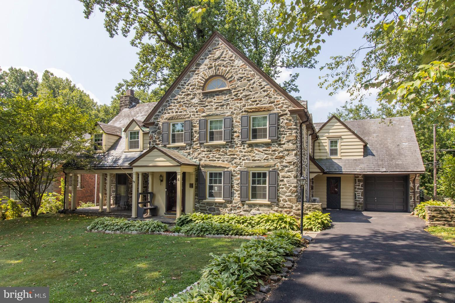 Charm & beauty fill this 5 bedroom 3/2 bath stone Tudor style home in the highly desired Lower Merion School District. Newer windows and doors (2018/2021), newer ductless HVAC system (2019), upgraded/replaced electrical (2017), freshly paved driveway (2021), and so much more! Fall in love with the grand entrance foyer leading to a U-shaped staircase with a beautiful palladian window.  Formal living room features a fireplace with a bonus room which makes a great office or playroom, and also leads to a covered front porch. Spacious formal dining room with wainscoting & crown molding, updated eat-in kitchen. Off the kitchen is a laundry room/mudroom, with an entrance from the driveway. The kitchen leads to the fenced-in backyard with deck and patio. Completing the first floor is a powder room. There is also a back staircase leading to the 5th bedroom that has its own bathroom and large closet - perfect in-law or au-pair suite. This bedroom can also be accessed through the 4th bedroom. The large master bedroom has 2 closets, an office nook, and en suite bathroom. 3 other bedrooms and a shared double vanity bathroom share the second floor landing along with pull down access to a very large stand up attic with finished floor and a walk in cedar closet. There are 2 staircases leading to the large finished basement with 2 rooms - one with a built-in bar and the other a perfect movie room, and a powder room. Home is 2882 sq ft plus the finished 700 sq ft basement. Located just blocks from Penn Wynne Library, Penn Wynne Elementary, multiple parks and shops. Slate roof currently being repaired and will be certified!