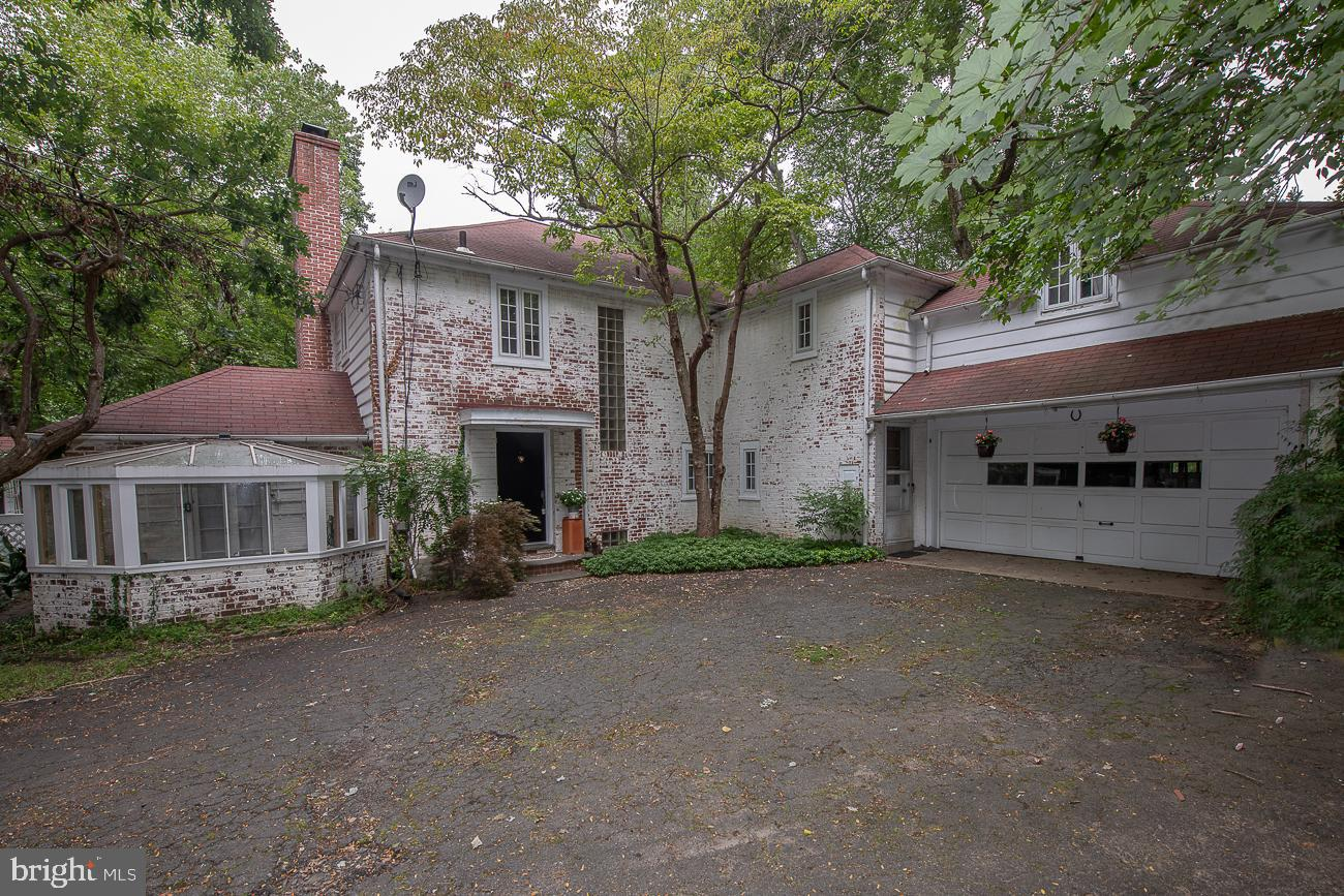 """Pulling into the driveway of this character filled, two story brick home you'll appreciate the private setting with its flowering bushes and mature trees.  Features include nearly 2600 sq. ft.  of interior space, generous room sizes, four fireplaces, random width hardwood floors, outdoor gathering space and a second structure, the summer house that would make a unique office or studio. The entrance foyer with a powder room welcomes you inside. Step down and turning left, the hallway leads to the den with a brick fireplace and custom built-ins and through glass French doors you access the green house with its separate heating zone. Straight ahead from the foyer is the oversized bright living room with a fireplace and outside exit to the flagstone patio with an outside fireplace and the summer house. The dining room is open to the living room, has its own access door to the back yard and flows into the breakfast room and kitchen. The laundry room and back stairs finish off this level. Up the curved staircase to the second floor, the primary suite consists of its own full bath with a stall shower, a dressing area with two closets, the main bedroom with two more closets and access to the second-floor covered balcony, a great place to have a cup of coffee overlooking the private, tranquil back yard. Down the hall you will find a hall cedar closet, hall linen closet, hall bath and the second bedroom that also opens up to the second-floor balcony. The third bedroom has two closets and the fourth bedroom, off the back stairs, has its own bathroom complete with a soaking tub.  The lower level offers a semi-finished room with a fireplace, a second semi-finished room, storage room and utility room.  Although currently occupied, this home is being sold in """"as-is"""" condition and will need some updating."""