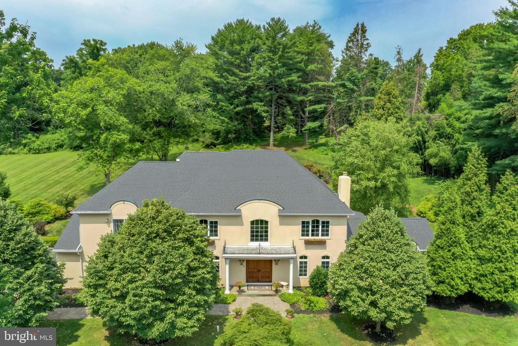 Welcome and come experience the true beauty and warmth of stunning Sunridge Estate in Schuylkill Township. This prestigious home is tucked away on a gorgeous 7 acre private lot with mature trees combined with sweeping views of the natural landscape, including the pond, creeks and multiple open spaces. The estate combines a modern custom architectural craftsmanship that was built in 2003  that blends an amazing floor plan to include an exquisite flow for this 5 bedroom, 4.5 Bath home with over 4800 square feet of living space. An incredibly functional floor plan, you will feel at home from the moment you enter.  There is a pride of ownership that is hard to find which is evidenced by how  the current owners have meticulously and lovingly maintained and modernized their property over the years. The stunning perennials, beautiful multi level paver hardscaping, pool, pond, creeks and huge open spaces, can be enjoyed from every window of the home. This truly secluded property features 2 structures: the main house plus the spring house offering limitless possibilities for future use. As you enter the main house through the majestic arched solid mahogany doors, you will note the grandeur is marked by a custom circular flying staircase with hand made wrought iron railing surrounded by spacious and elegant rooms, soaring ceilings, exotic hardwood floors, 3 working fireplaces, large deep windows sills, beautiful built ins, crown moldings throughout and more. Along with the formal dining room appointed by a professional interior designer & spacious home office with a stone fireplace, you will find a sun drenched great room with a custom marble fireplace flanked by huge French doors on two sides opening to the patio, as well as an entrance to the sunroom.  The gourmet kitchen features a fabulous chef's eat in kitchen with a center island and built in vegetable sink, high end appliances including a Viking double oven and 8 burner stove, Subzero double door refrigerator and addit