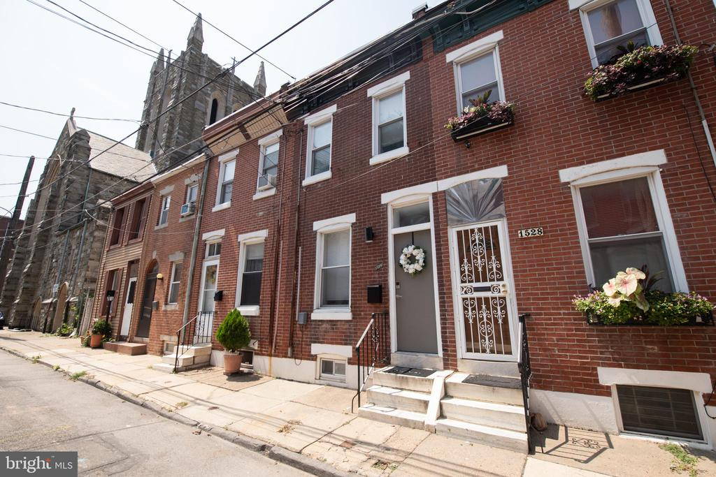 Welcome home to this beautiful two bed, two and half bath home in the hip and sought after neighborhood of Fishtown. Enter into the open floor plan boasting character with exposed brick wall and unique metal and wooden staircase that will surely be a conversation piece. Natural light streams through the two large front windows to accent the gleaming hardwood floors in this space that will be perfect for both your relaxing and entertaining needs. Head through to the modern kitchen with granite counters, tile backsplash,  stainless steel appliances, gas cooktop, and recessed lighting. Off the kitchen, you will find a private and inviting patio for your backyard gatherings or morning coffee.  Back inside and up the one of a kind wooden and metal staircase you will find two bedrooms, and not one, but two FULL baths. The upstairs boasts hardwood floors throughout and recessed lighting. The first bedroom is large,  filled with sunlight, and has a nice-sized closet.  The first full hall bath is updated with deep, tiled shower. The second full hall bath is large with glass and tiled shower. The second bedroom features recessed lighting, closet, and slider glass doors that open up to the bonus upstairs deck. Freshly stained and with magnificent views, this deck is a wonderful added surprise. The basement is unfinished but neat, with washer and dryer and tons of storage space. Not only is this home move in ready, with finished floors and fresh paint throughout, but also just had a BRAND NEW roof put on with 20 year warranty. This hidden gem sits on a cute and quiet street, yet is an easy walk to endless shops, restaurants, gyms, and transportation. The convenience of a nearby SEPTA stop has you downtown in minutes, and you also have easy access to 95 and other major highways. This home will not last. Make your appointment today!