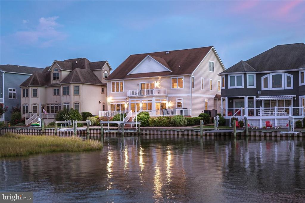 Exquisite custom built 5BR/4.5BA waterfront estate in Ocean City, Maryland hits the market!  Immerse yourself in the ambience of this luxurious waterfront lifestyle while enjoying breathtaking views of the water and enchanting bird sanctuary. This property features exceptional craftsmanship and was custom built by T&G Builders with astute attention to detail. This home is built for the sophisticated buyer looking for custom finishes, such as the grand curved staircase fit for a princess.  This home has plenty of space for family and friends, and features five bedrooms with the master bedroom and bath on the first floor.  The second floor family room is currently being used as a game room but could be a sixth bedroom if needed. There is also a home office perfect for the remote worker in today's world.  The incredible kitchen has granite countertops, stainless steel appliances, high end cabinets, breakfast bar, double ovens,  and many other upgrades. The dining area is off the kitchen and provides expansive water views.  The family room is off the dining room and also overlooks the water. The family room has a gas fireplace for enjoying winter nights relaxing at home.  Enjoy outdoor living with the maintenance free multi-level decks perfect for summertime barbecues, parties, crab feasts, entertaining and relaxing. There's your own private pier with a deep water dock, boat lift, two jet ski lifts and vinyl bulkhead. In the front of the house there is a covered porch creating a warm environment, and the home has been professionally landscaped. This estate offers a fabulous open floor plan that maximizes spectacular views.  There is plenty of storage and you will love the full walk-up steps to the floored attic with high ceilings.  This home is in the amenity rich community of Heron Harbour. The community amenities include an indoor heated pool, outdoor family pool, Olympic size lap pool, kiddie pool, fitness center, library, social room and two lighted clay tennis cour